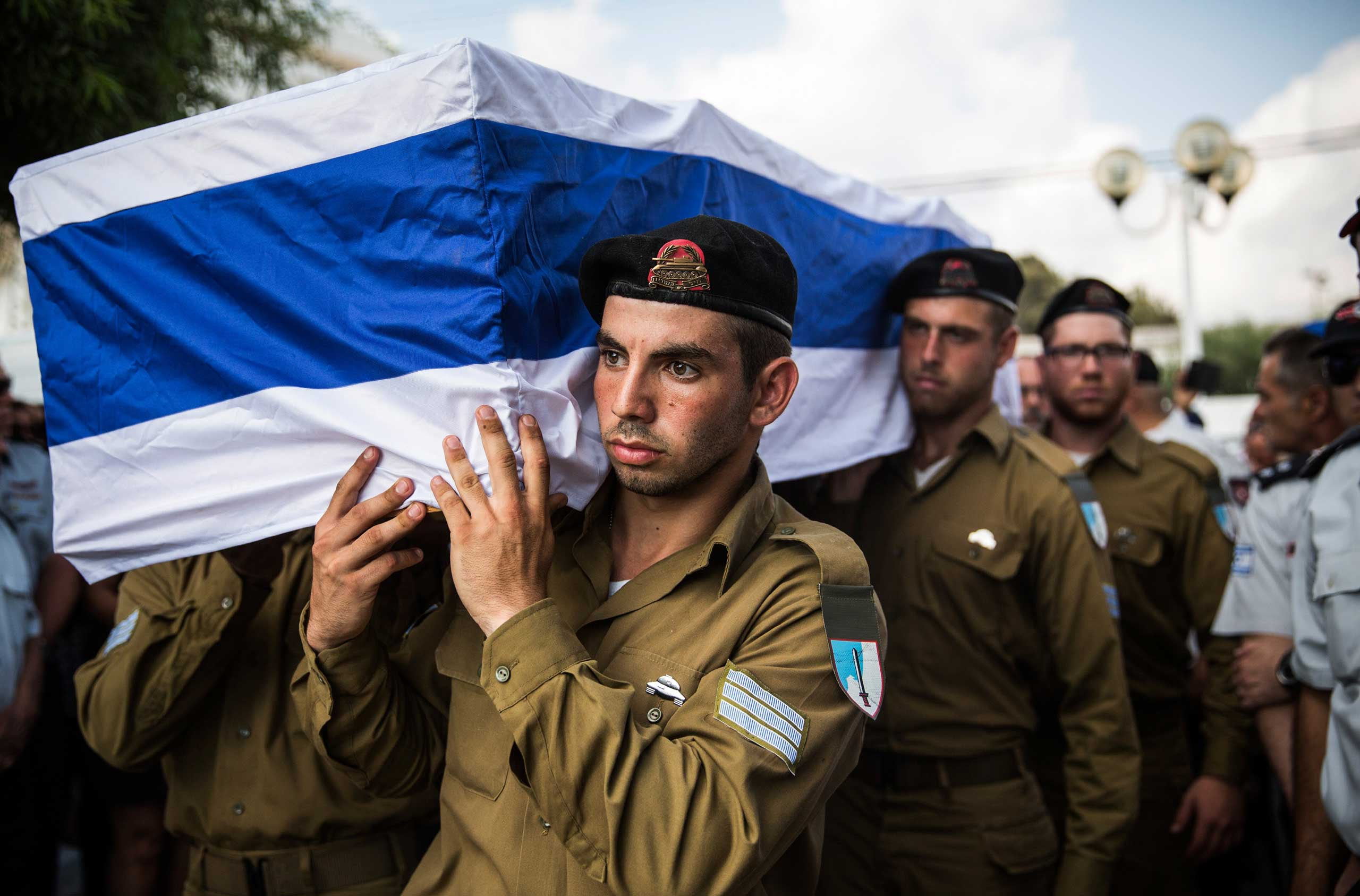 The casket carrying Israeli Sergeant Adar Barsano is carried to a burial plot in a cemetary during his funeral in Nahariya, Israel, July 20, 2014.