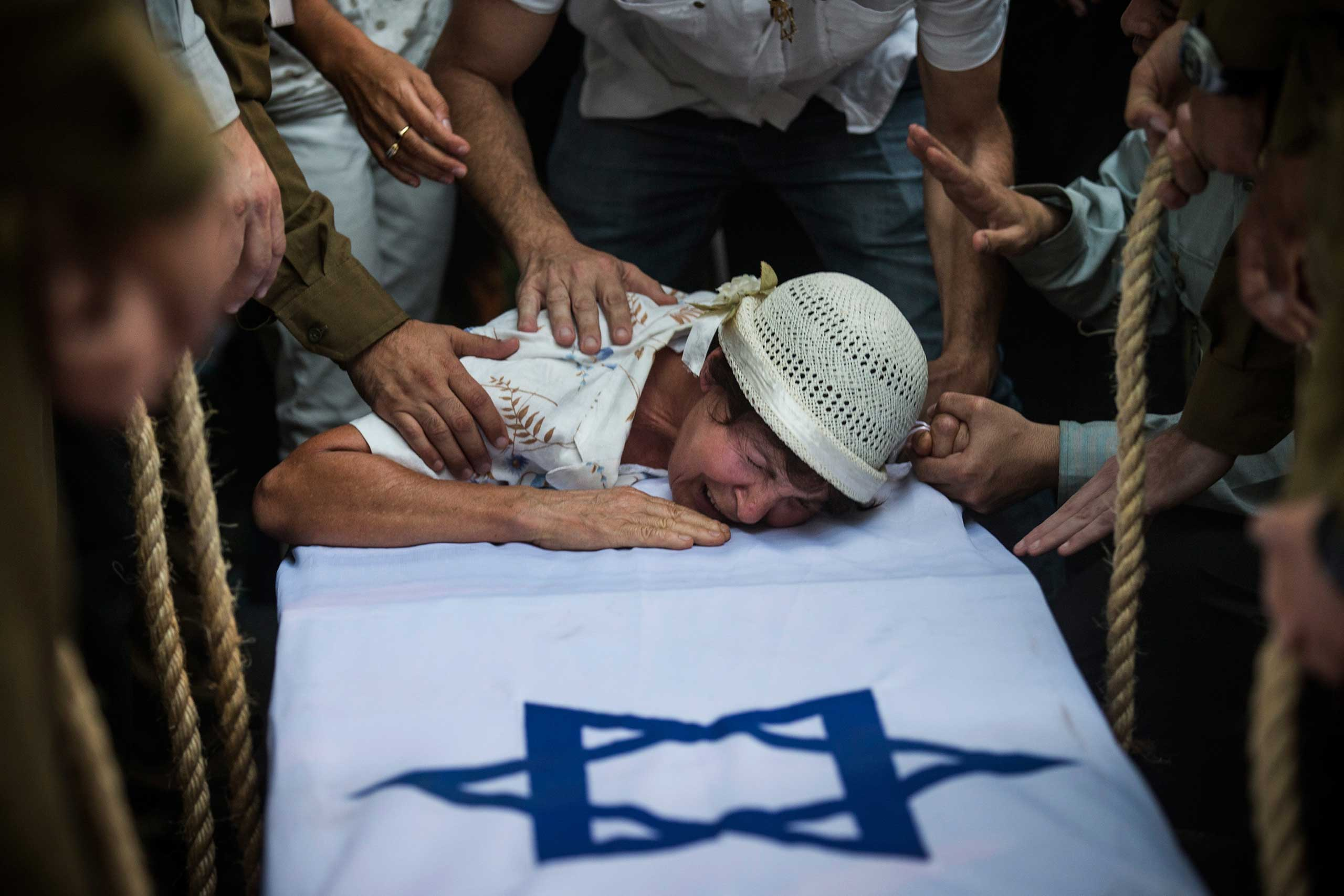 The grandmother of Private First Class Jordan Bensimon, cries over his casket during his funeral in Ashkelon, Israel, July 22, 2014.