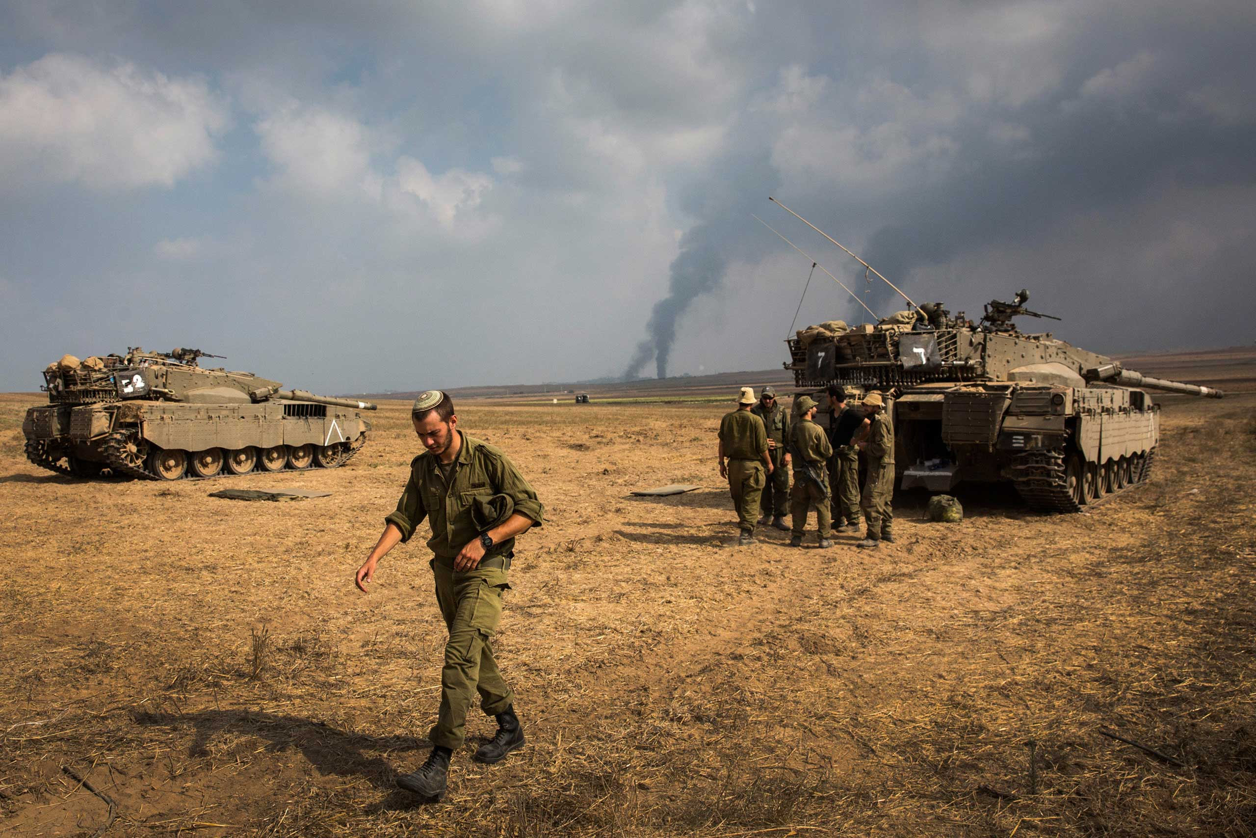 Israeli soldiers stand near their tank while smoke due to airstrikes and shelling rises from Gaza near Sderot, Israel, July 22, 2014.