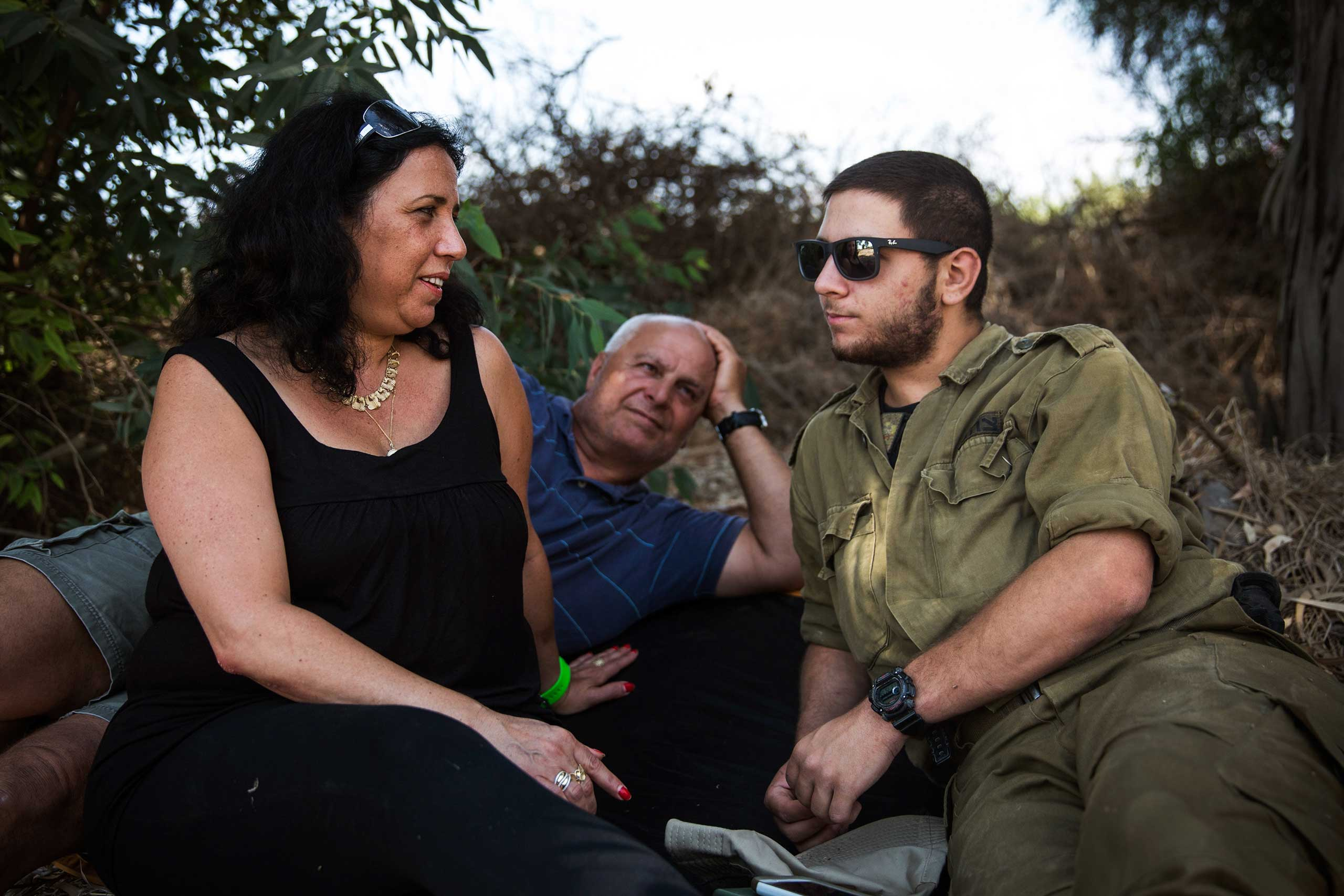 Ruty Friza and Pini Friza meet with their son, First Lieutenant Ziv Friza during a 12-hour ceasefire just outside the militarized zone close to the Israel-Gaza border near Kfar Aza, Israel, on July 26, 2014.