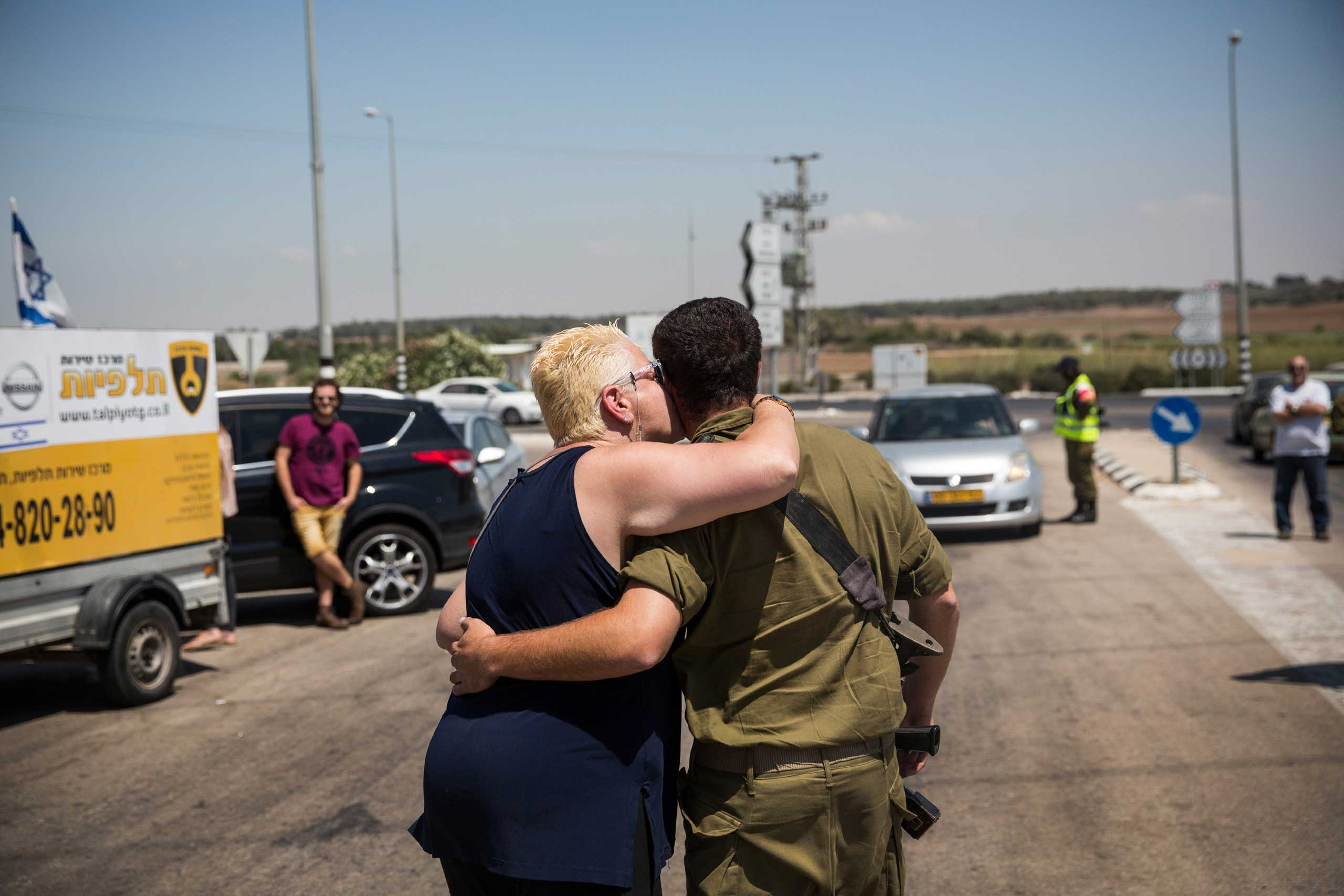 A soldier meets with his loved ones during a 12-hour ceasefire just outside the militarized zone close to the Israel-Gaza border near Zikim, Israel, July 26, 2014.