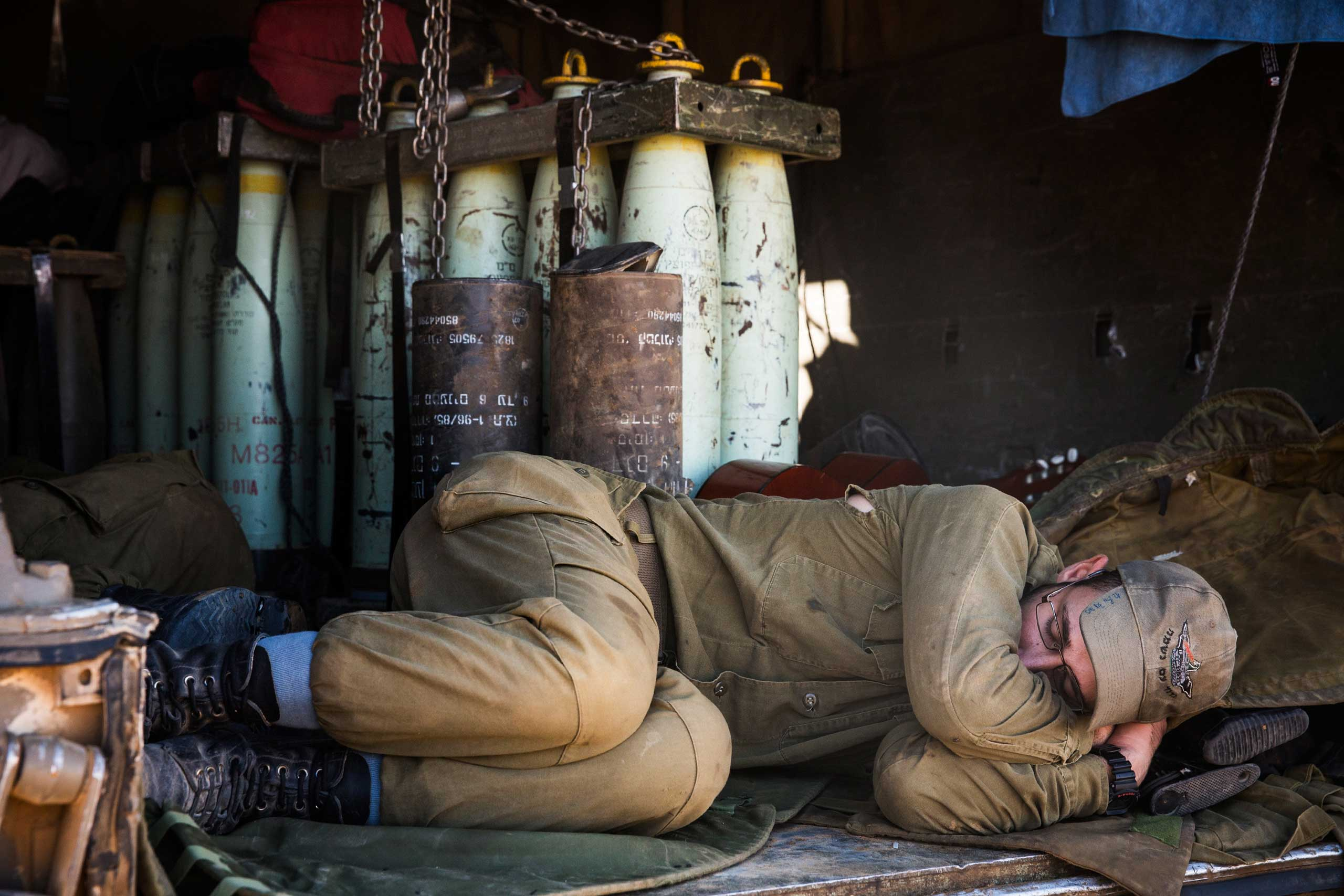A soldier sleeps next to artillery shells close to the Israel-Gaza border near Sderot, Israel, July 19, 2014.