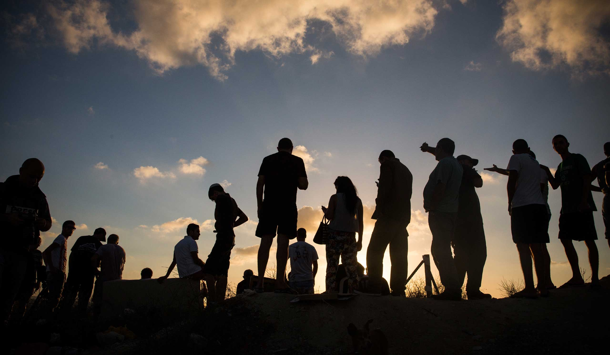 Civilians and members of the media wait to see Israeli attacks inside Gaza from the top of a hill on the sixth day of Israel's operation 'Protective Edge' in Sderot, Israel, on July 13, 2014.