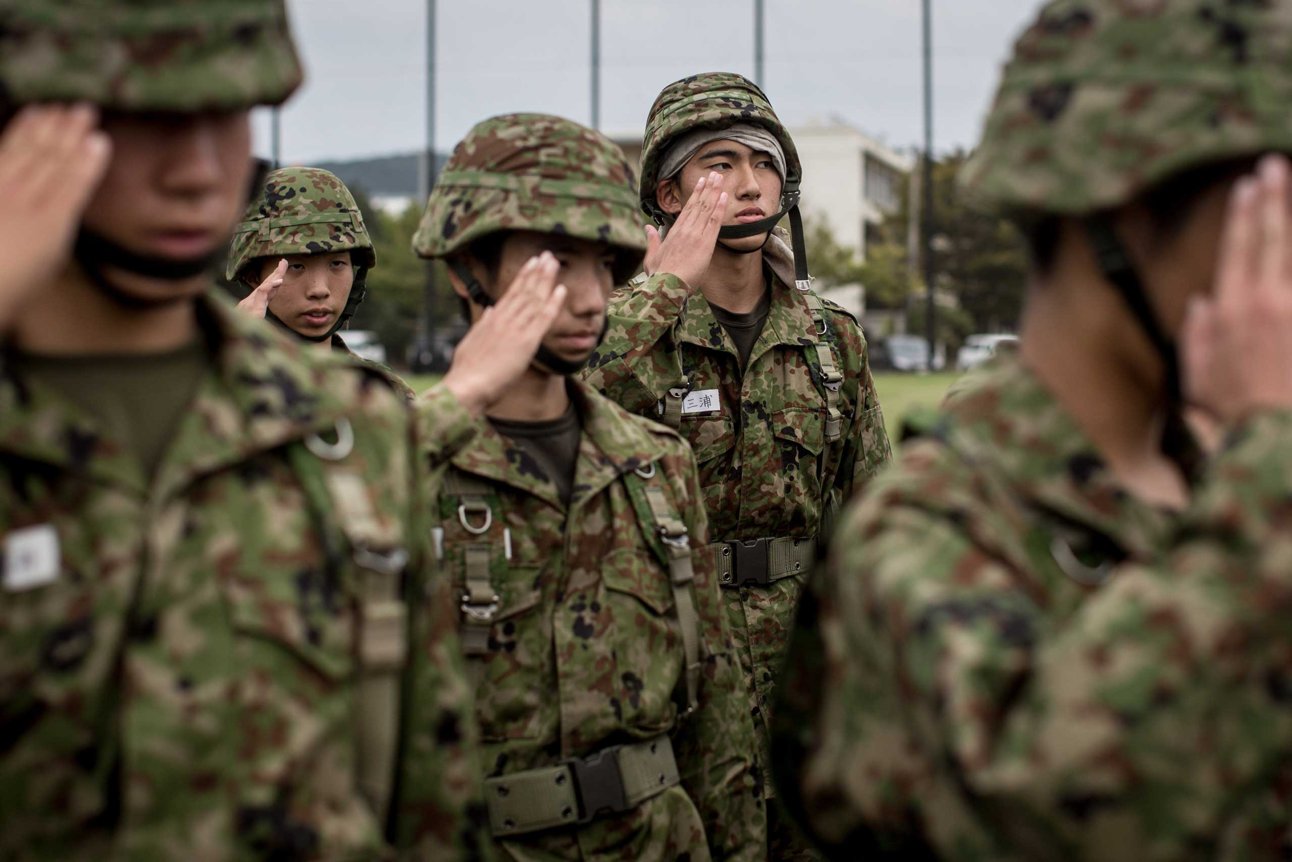 Students salute their teacher after finishing rifle training.