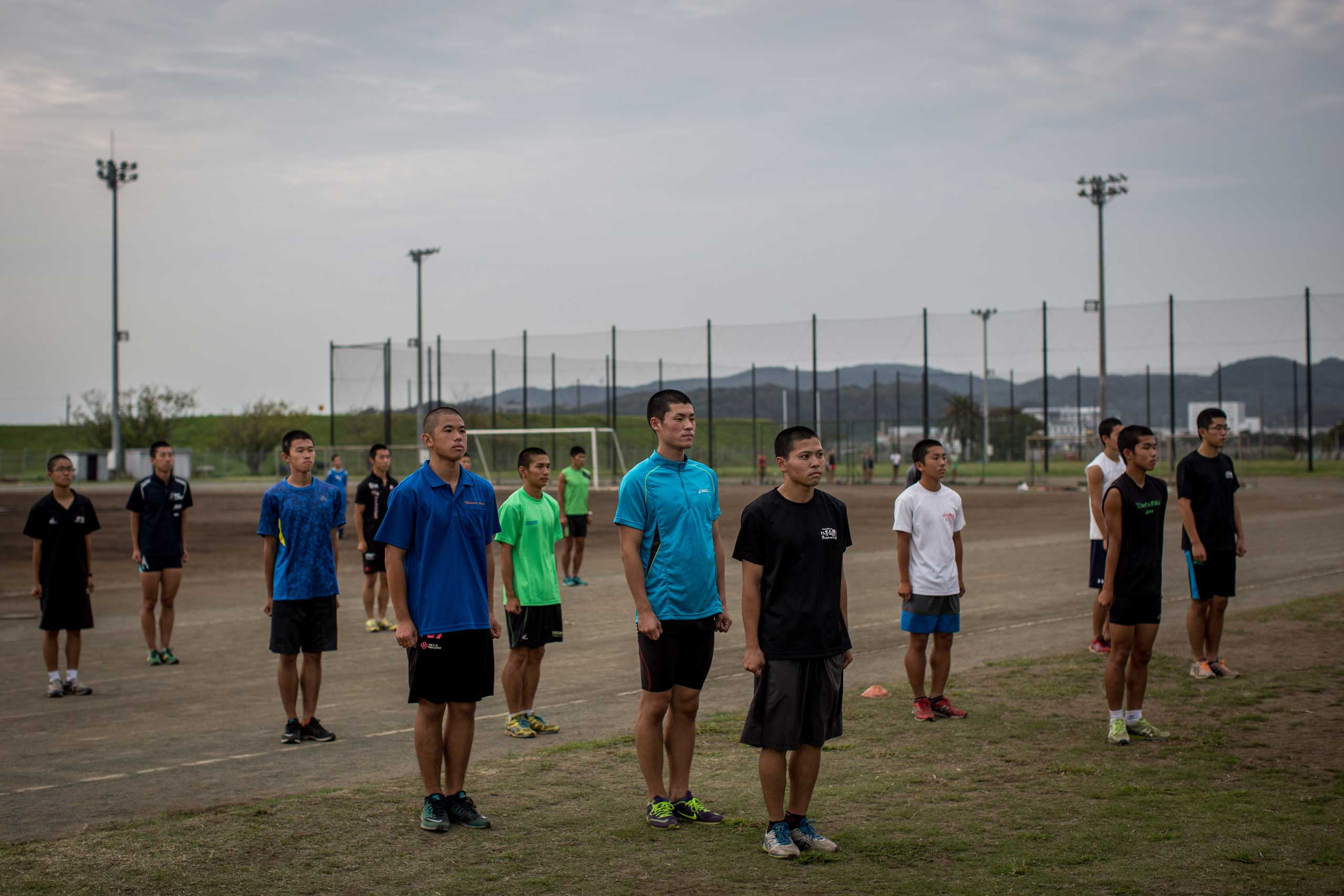 Students stand to attention while the schools song is played over loudspeakers during track and field training.