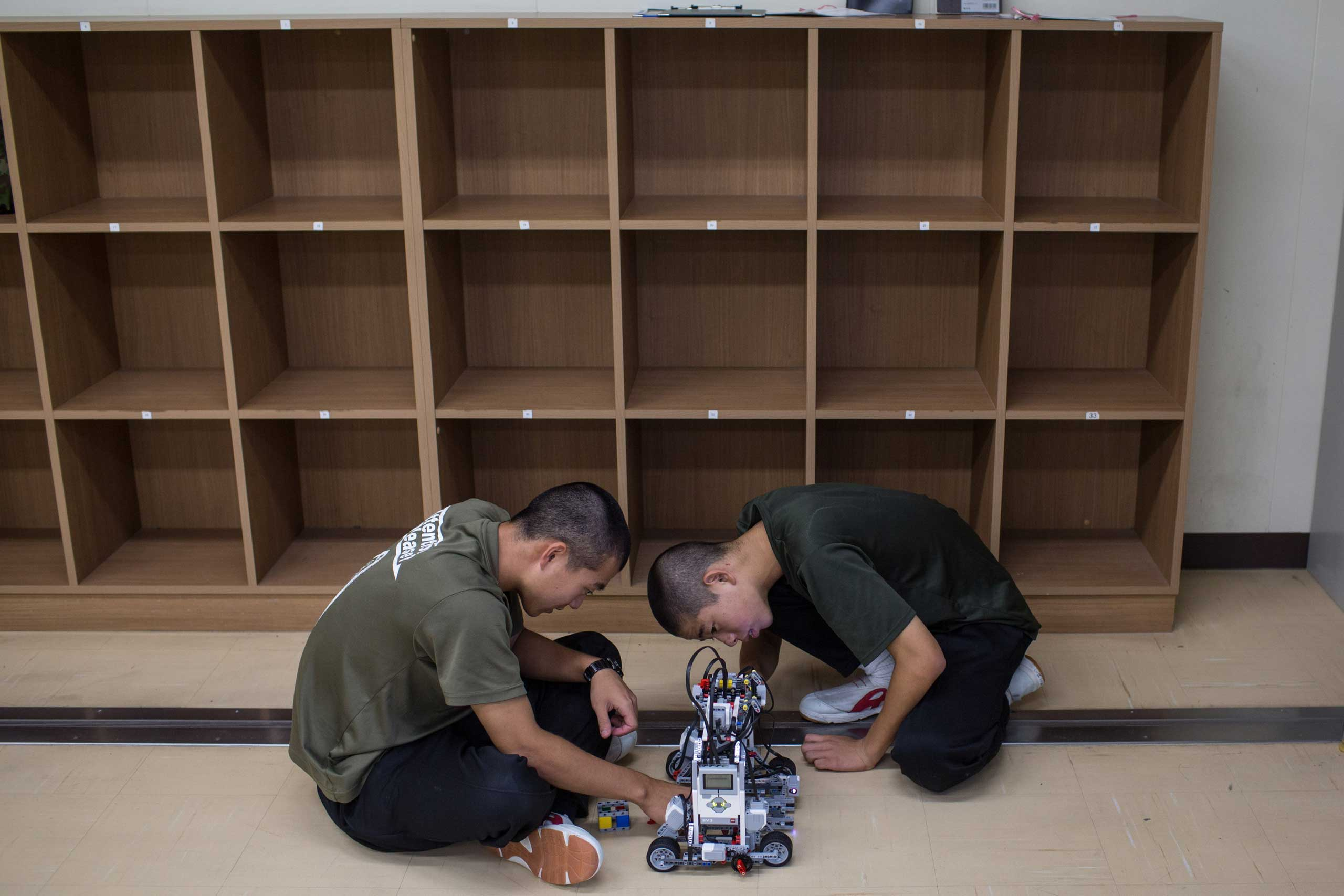 Students work on a robot during robotics classes.