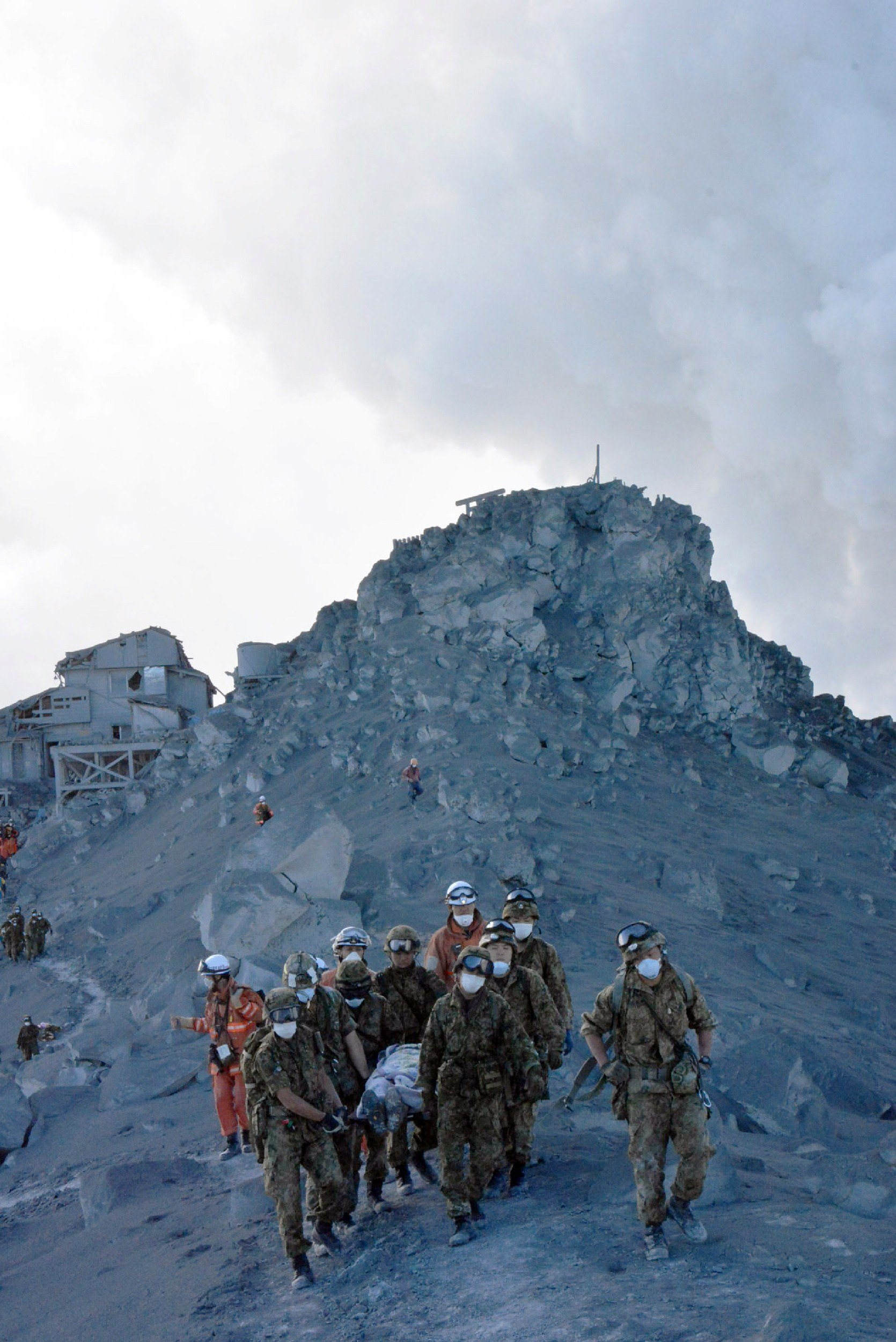 Japan's Self Defense Force soldiers carry an injured climber from the ash covered top of Mount Ontake at Nagano prefecture, one day after Japan's volcano Ontake erupted in central Japan, Sept. 28, 2014.