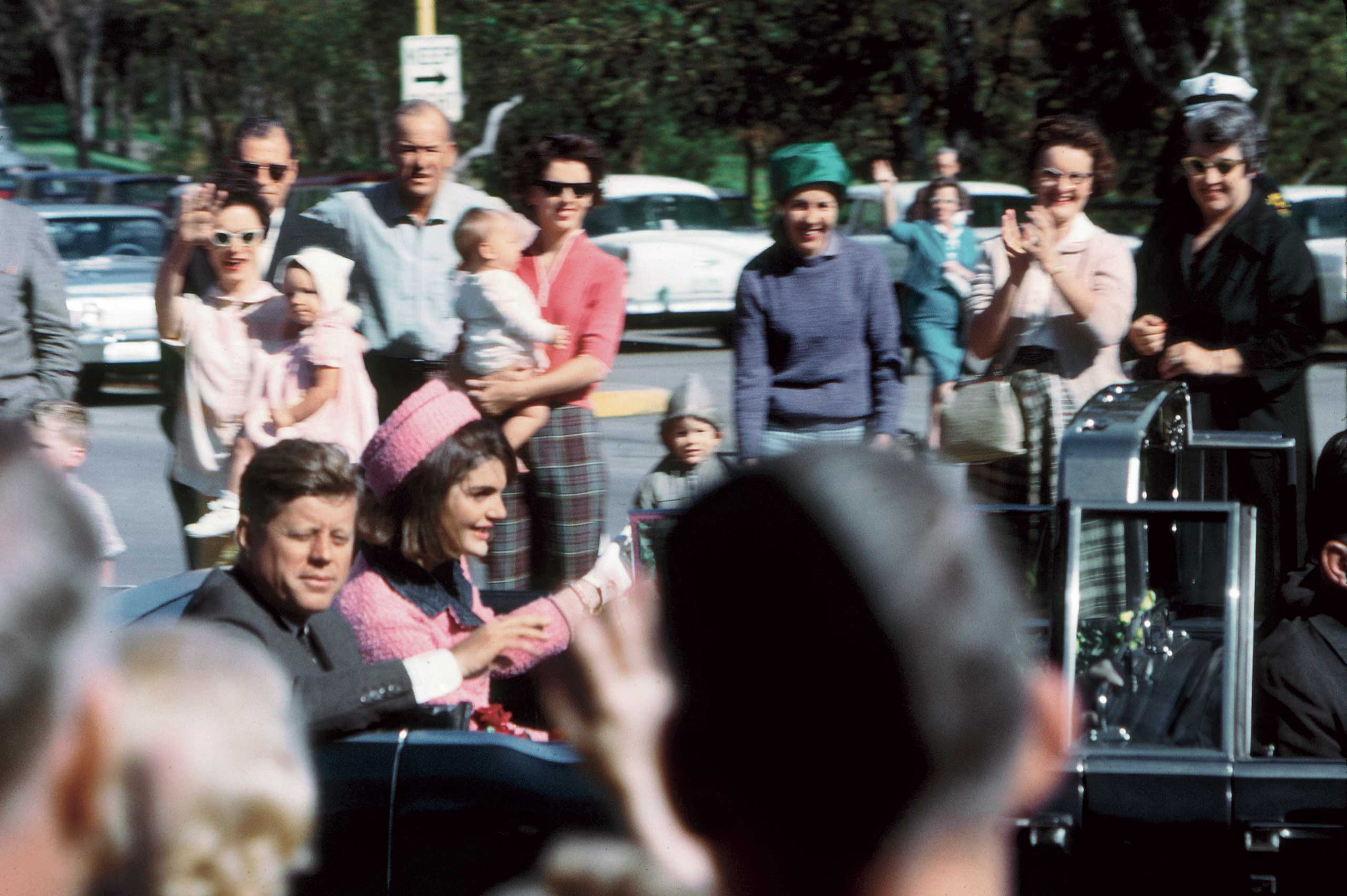 Kennedy's well-wishers crowded close to his limousine as the motorcade neared Dealey Plaza.