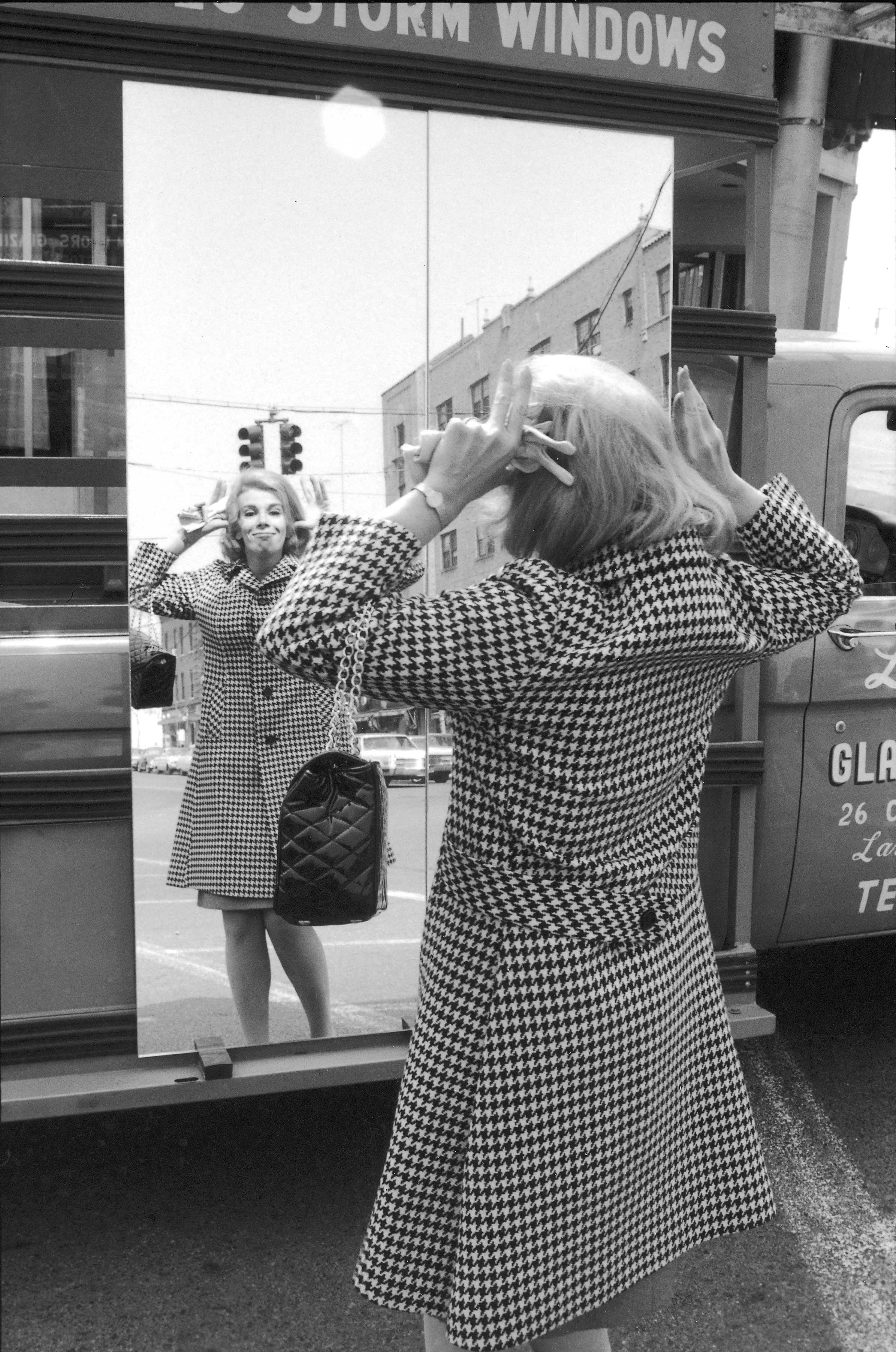 Comedienne Joan Rivers making faces in a mirror on the street in New York City on March 1, 1966.
