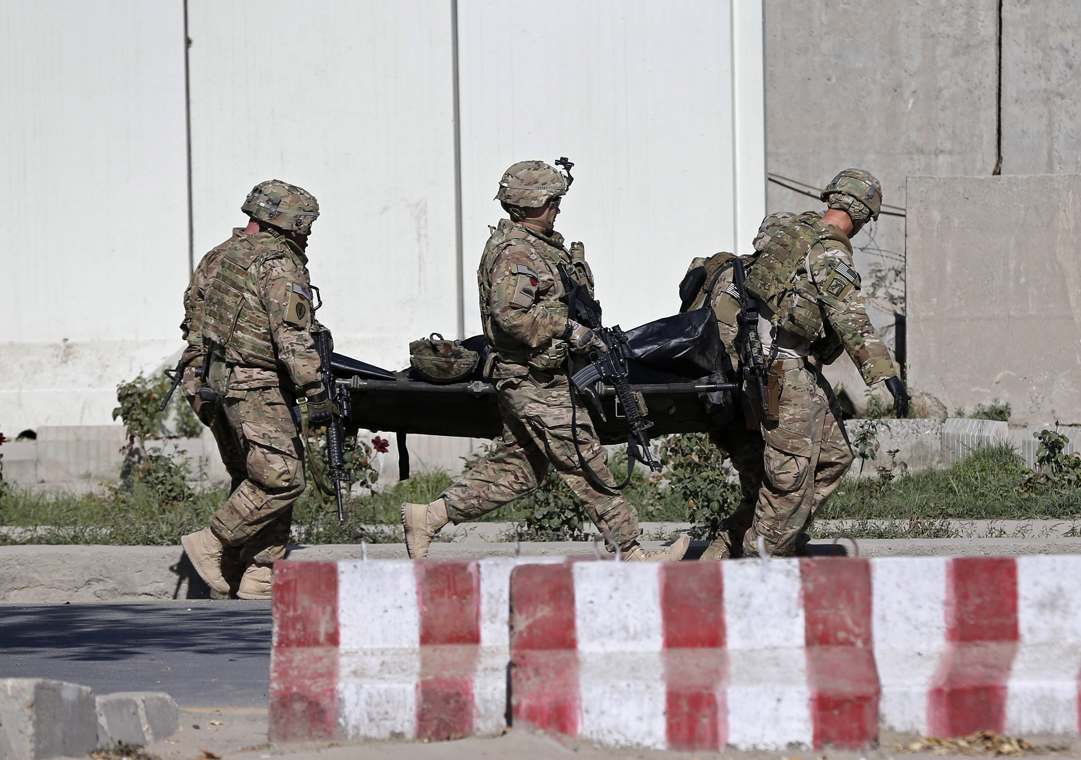 U.S. troops carry the dead body of a member of an international troop at the site of suicide attack in Kabul September 16, 2014.