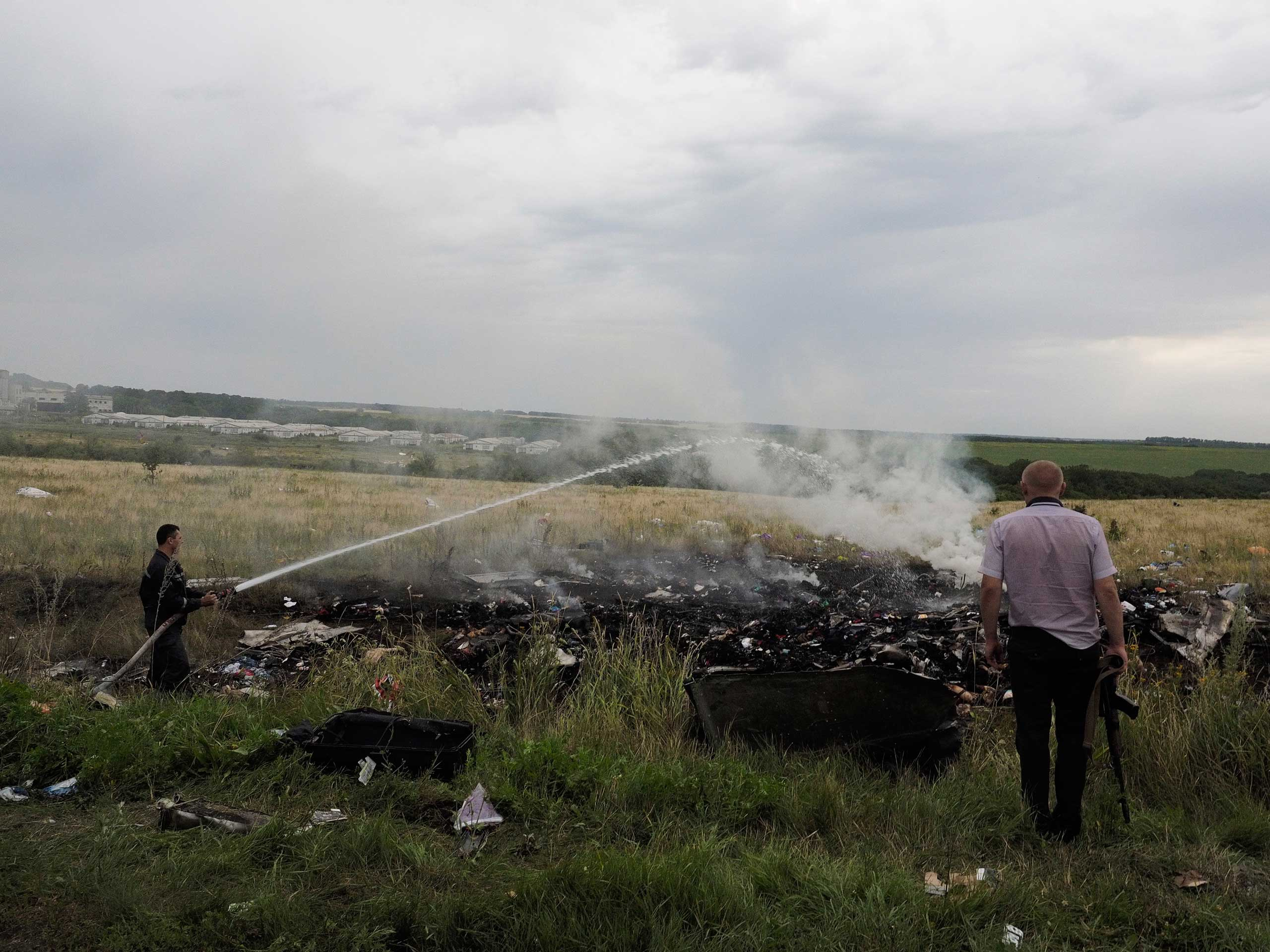 A firefighter and an armed man look at the remains and the corpses of passengers aboard Malaysia Airlines flight MH17 that was shot down over eastern Ukraine, July 17, 2014.