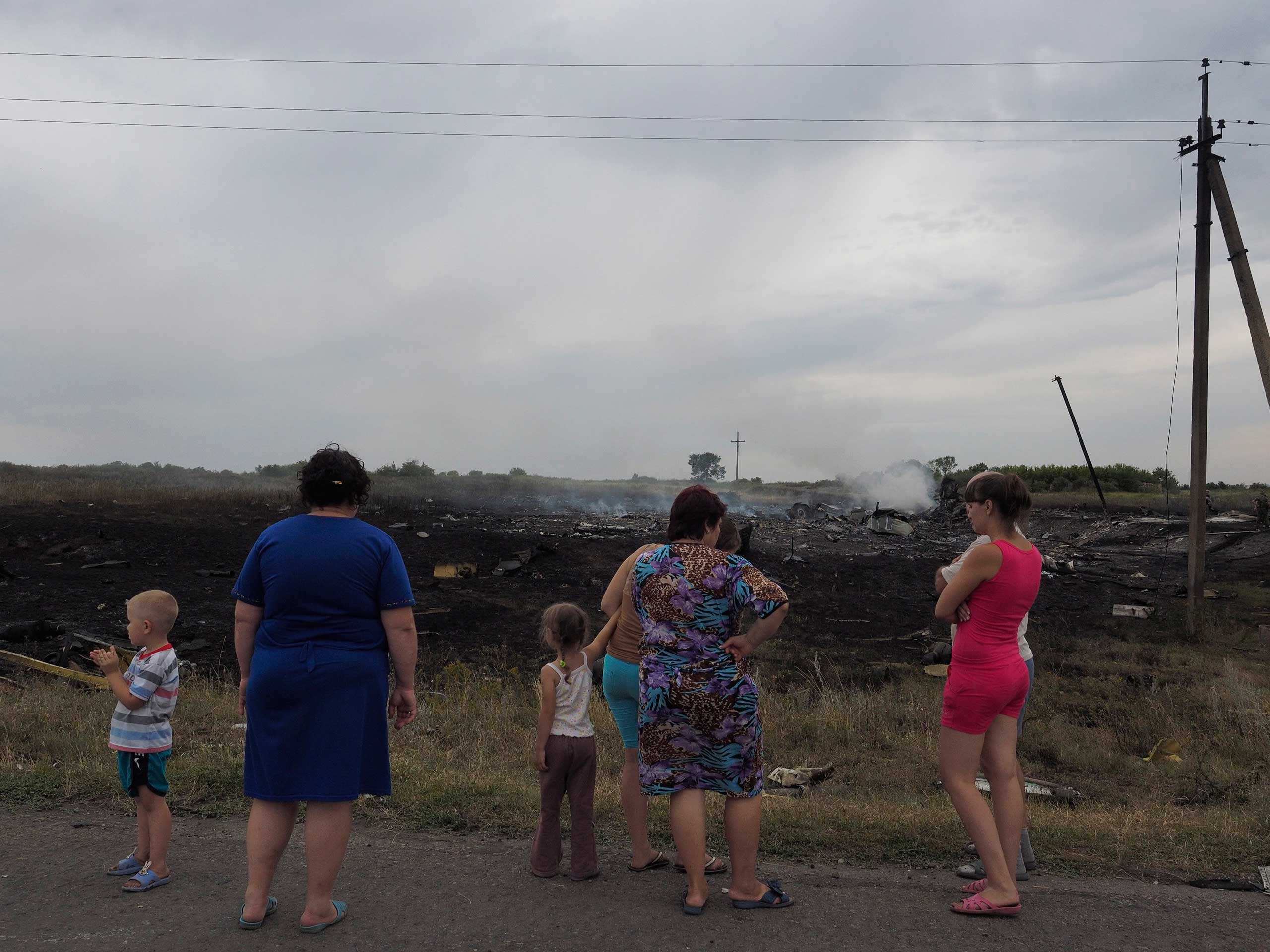Locals at the crash site of Malaysia Airlines flight MH17 carrying 298 passengers that was shot down near the village of Grabovo, eastern Ukraine, July 17, 2014.