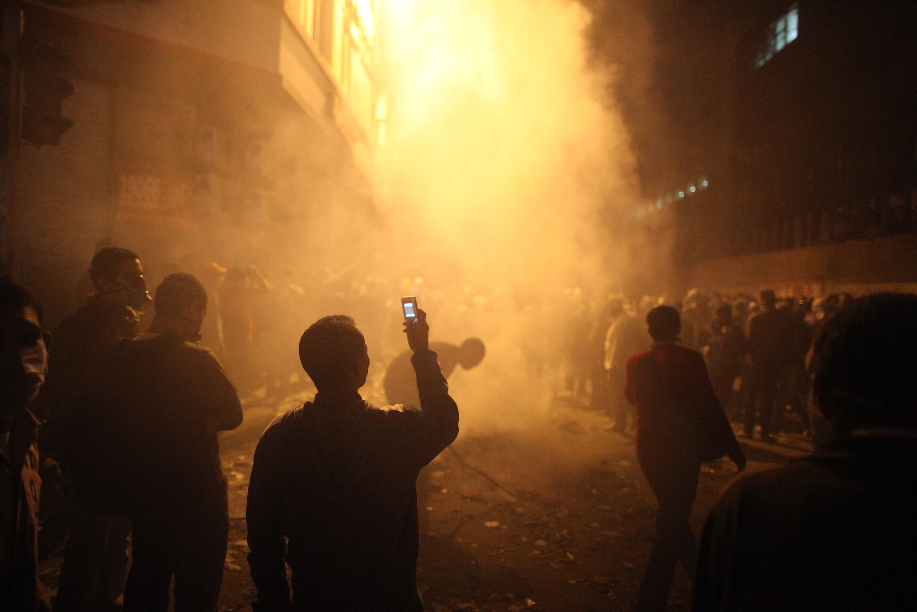 <strong>2011</strong>                                   A youth films the aftermath of tear gas police fired at protestors in Muhammed Mahmoud Street near Tahrir Square on November 23 in Cairo.