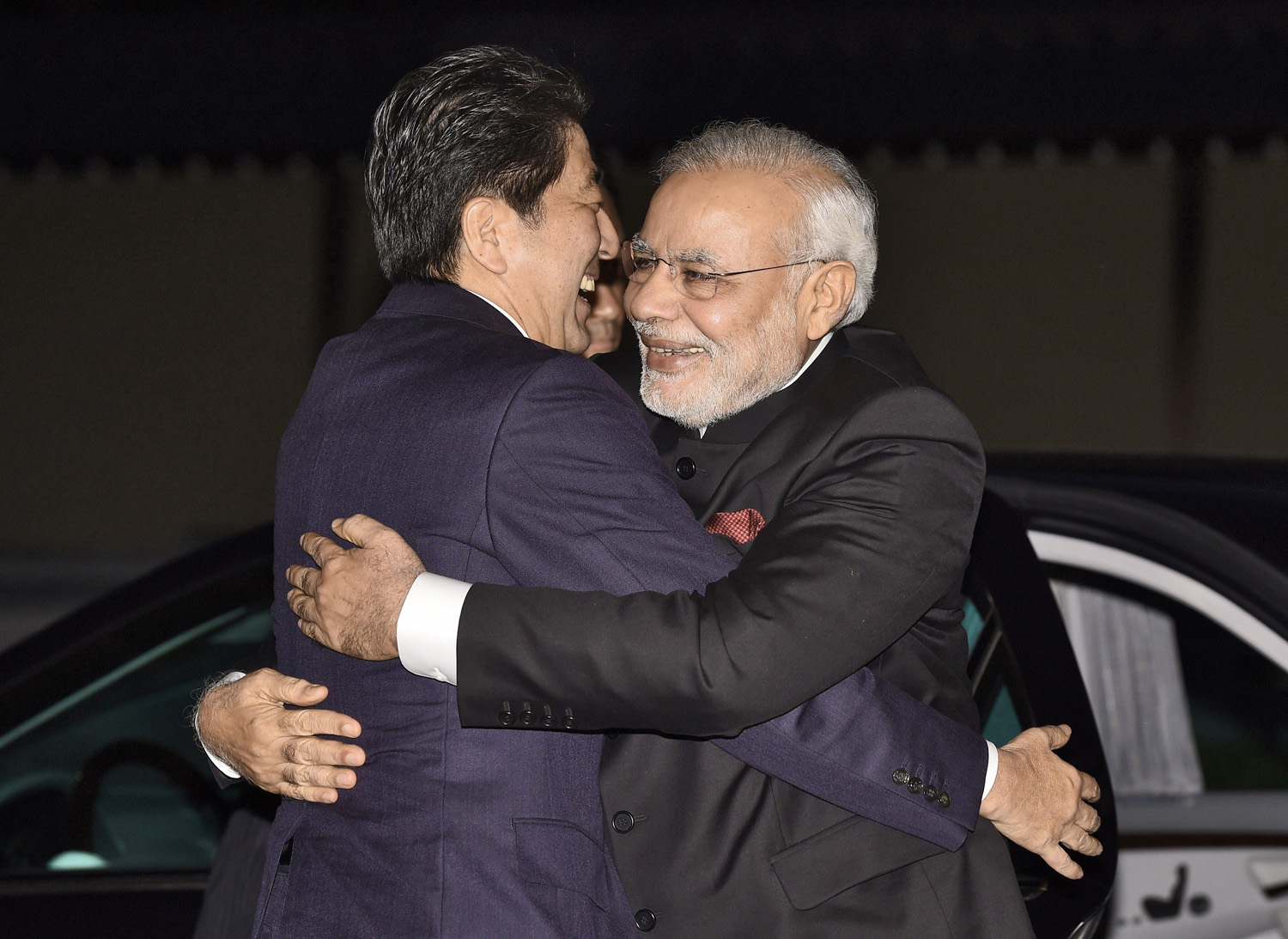 Japan's Prime Minister Shinzo Abe hugs Modi upon                      his arrival at the state guesthouse in the Japanese city of Kyoto