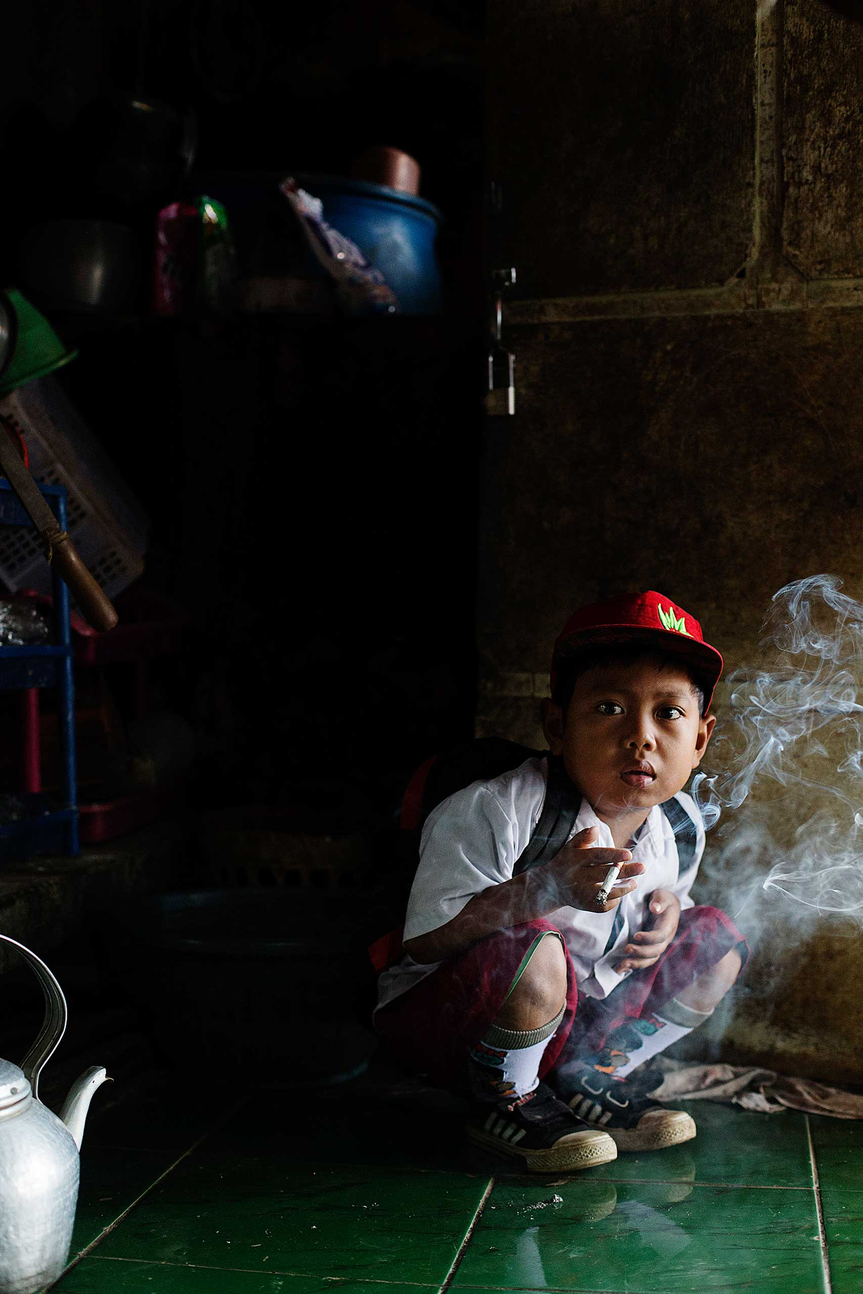 Dihan Muhamad has his first cigarette at 7AM at his home before he attends his first grade class in his village near the town of Garut, Indonesia on February 10, 2014.