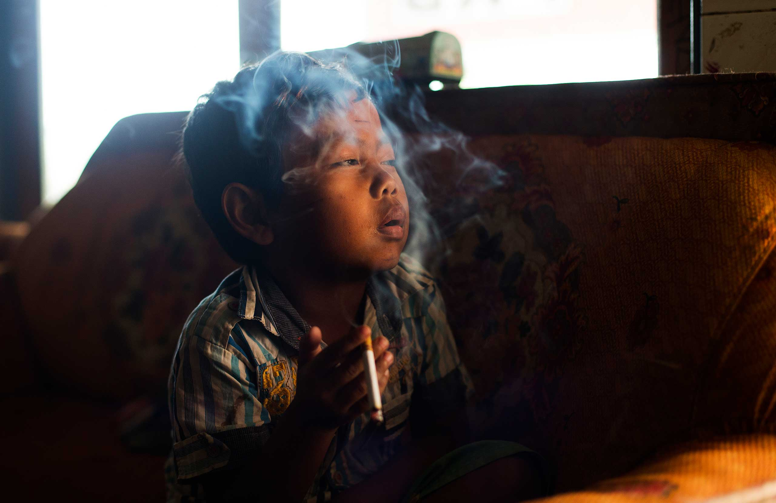 Dihan Muhamad smokes in his home in a village near the town of Garut, Indonesia on February 10, 2014.