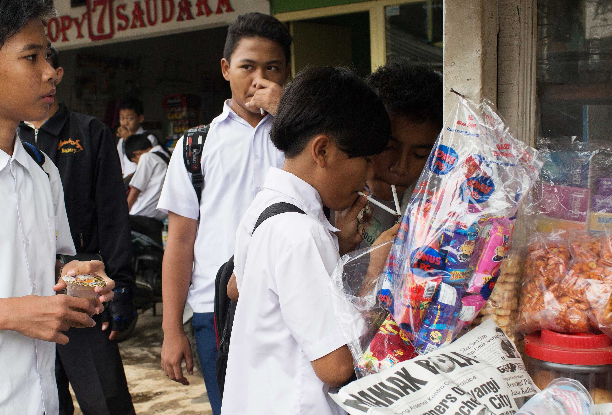 Groups of children buy single cigarettes and light them at a kiosk after school on February 12, 2014 in Jakarta, Indonesia. The children purchased cigarettes here without age identification and kiosks such as this one can be found near schools around the city.