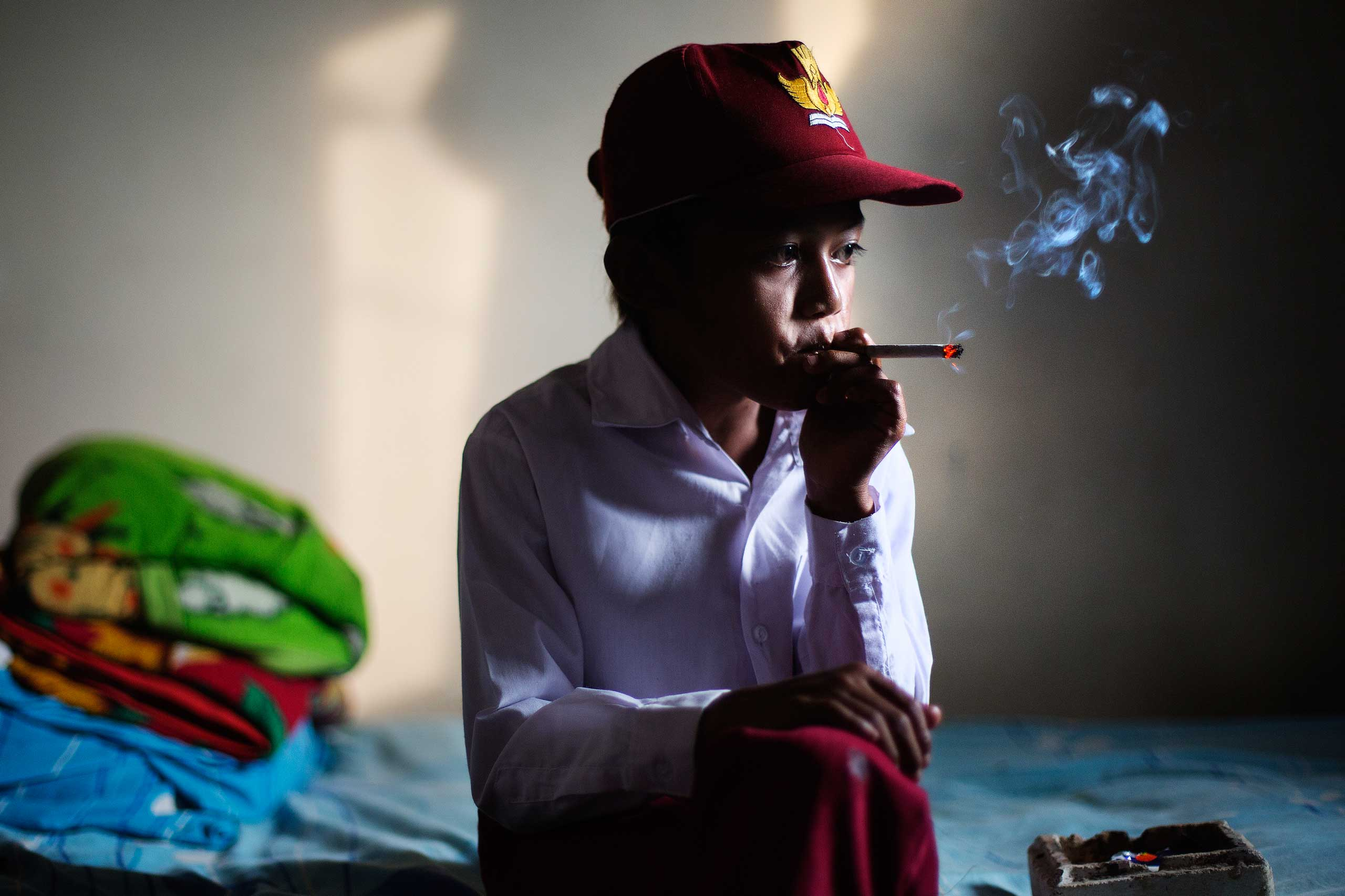 Ilham Hadi, who has smoked up to two packs a day and began when he was four years old, poses for a photo wearing his third grade uniform while smoking in his bedroom in a village near the town of Sukabumi, Indonesia on February 14, 2014.