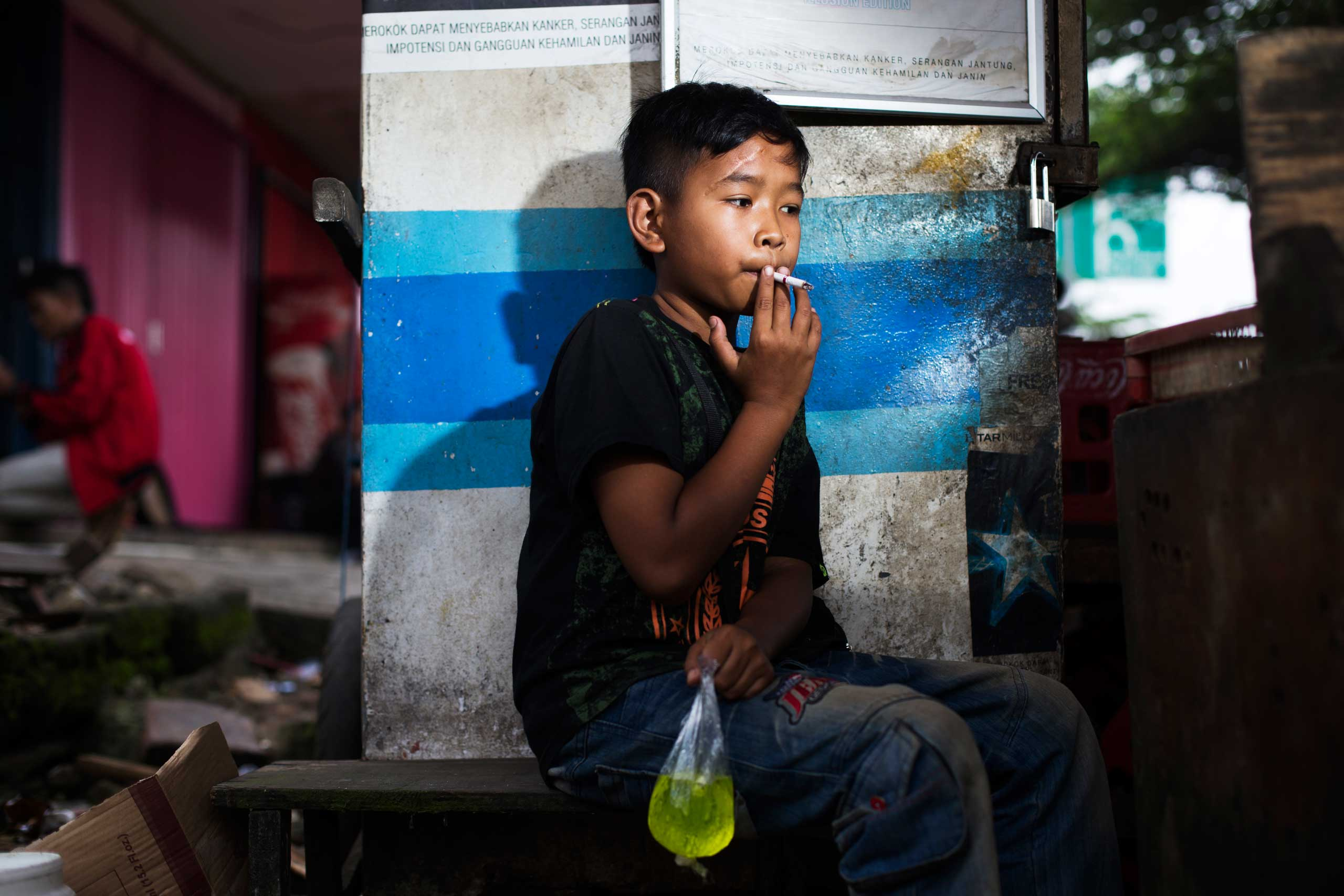 Eman poses for a photo as he smokes a cigarette while clutching a bag of juice in east Jakarta, Indonesia on February 12, 2014.