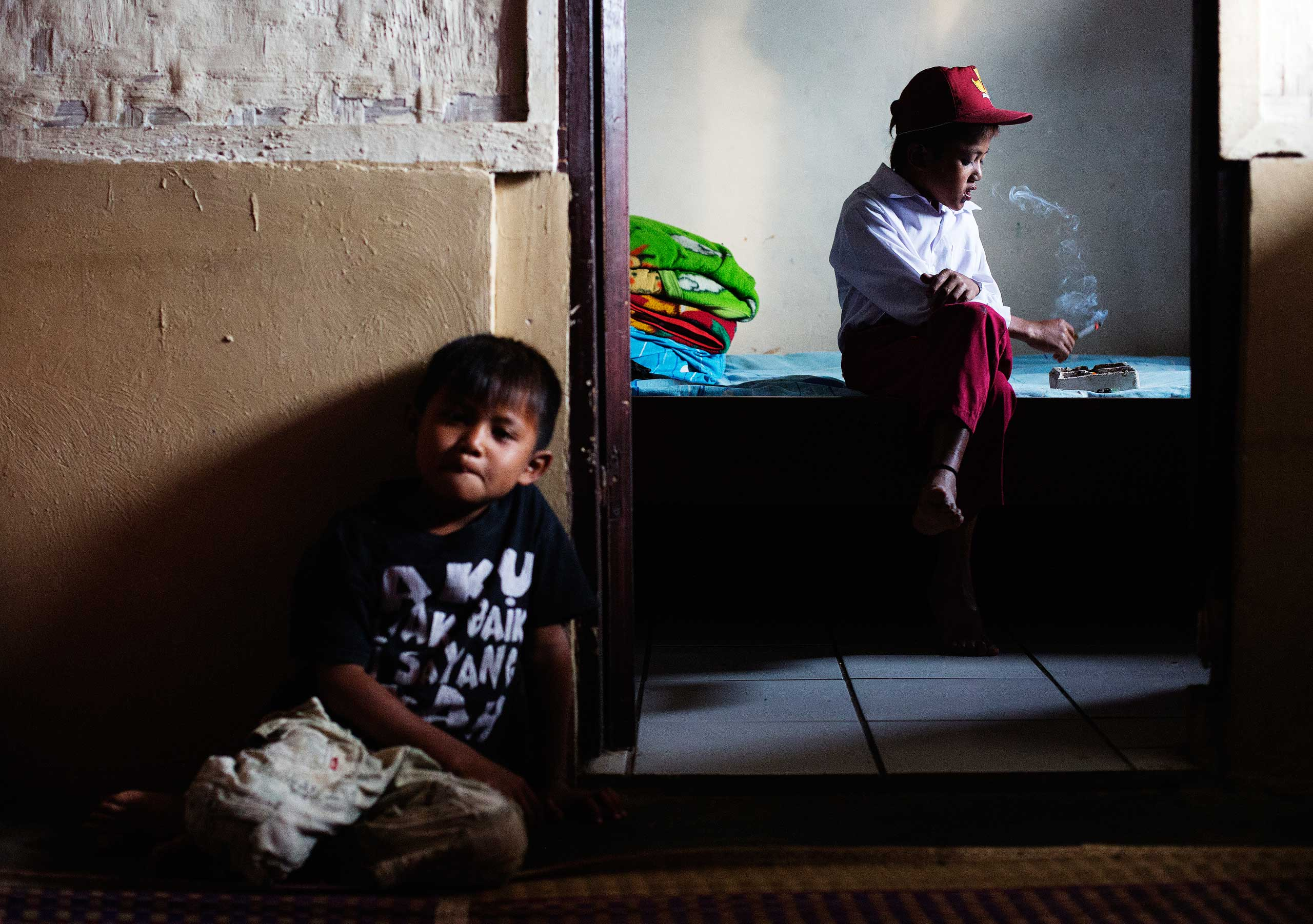 Ilham Hadi, who has smoked up to two packs a day and began when he was four years old, poses for a photo wearing his third grade uniform while smoking in his bedroom as his younger brother looks on in their village near the town of Sukabumi, Indonesia on February 14, 2014.
