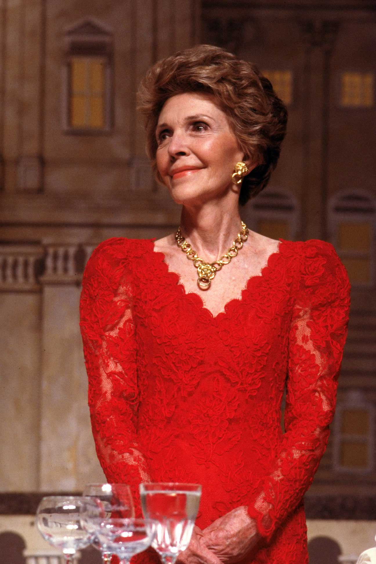 Nancy Reagan, decked out in red lace dress, gold earrings and necklace set, at  President's dinner  in Washington on May 11, 1988.