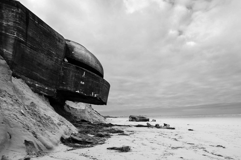 A concrete bunker used by the German Army in WWII sits precariously on top of an eroding sea front in France along the route of the Atlantic Wall (Atlantikwall in German).