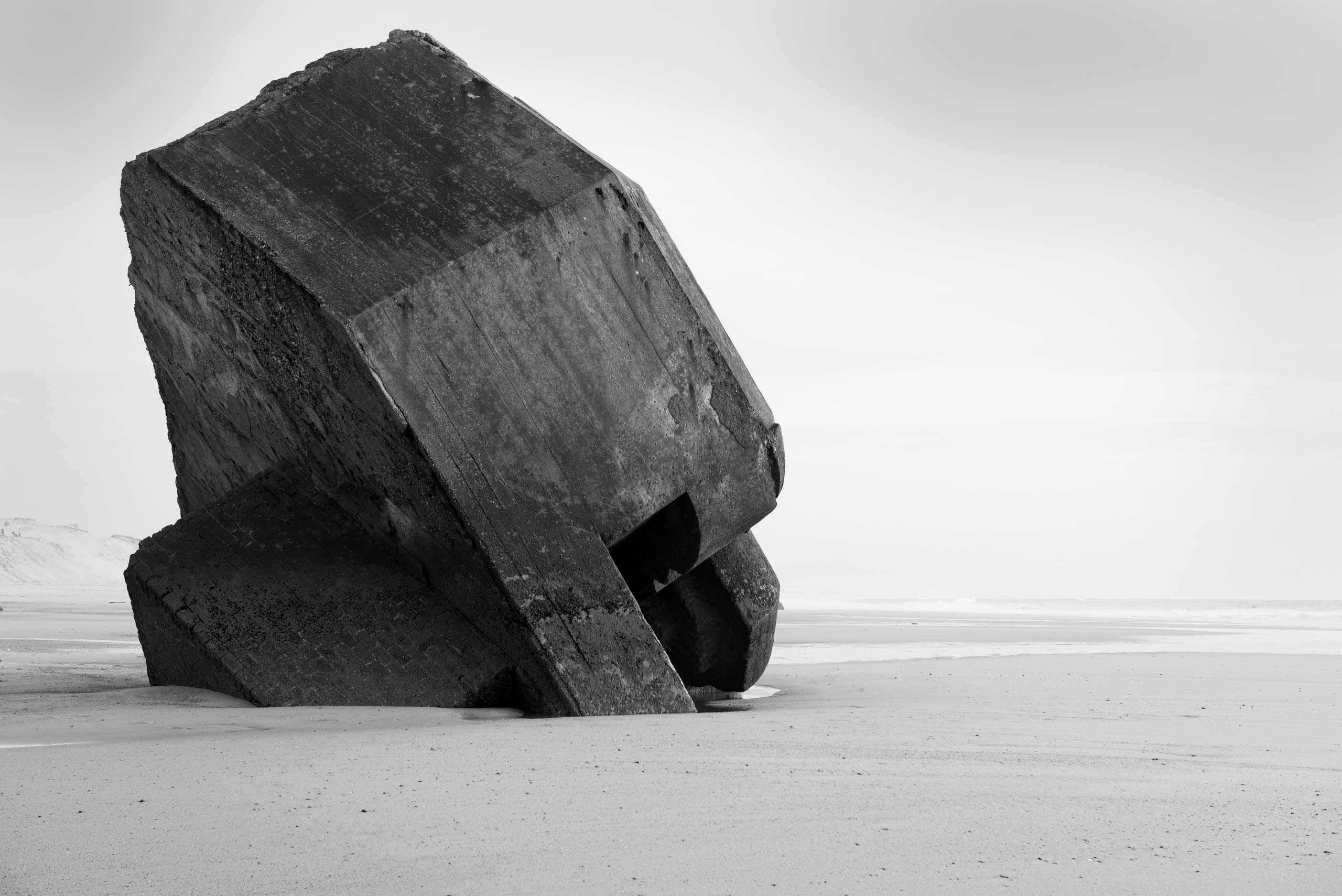 The remnants of a concrete defensive structure used by the German Army during World War II juts out of the sand along a beach in nothern France along the route of the Atlantic Wall (Atlantikwall in German).