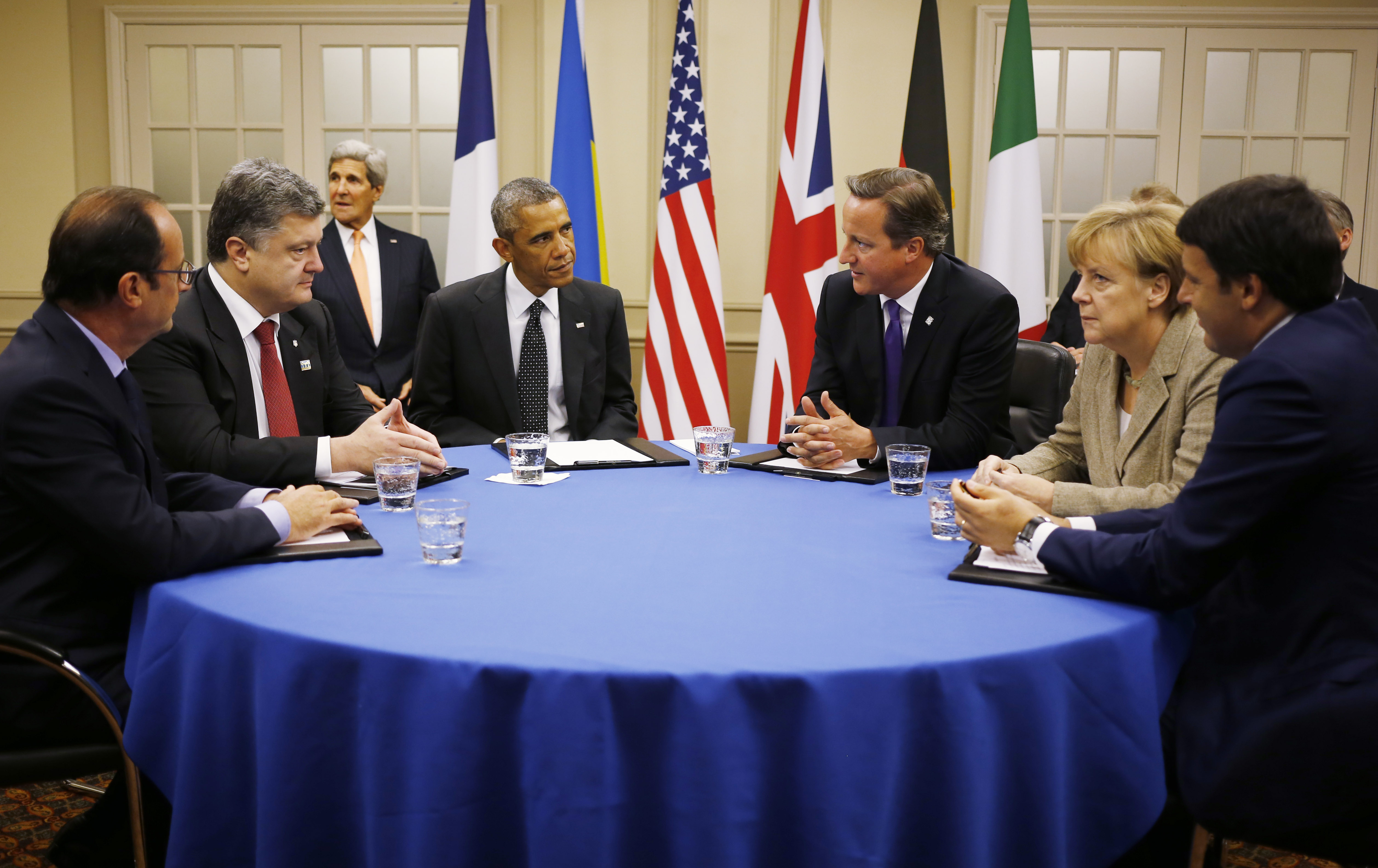 President Barack Obama is seated at a table with, from left to right: France's President Francois Hollande; Ukraine President Petro Poroshenko; British Prime Minister David Cameron; German Chancellor Angela Merkel; and Italian Prime Minister Matteo Renzi as they meet about Ukraine at the NATO summit at Celtic Manor in Newport, Wales on Sept. 4, 2014.
