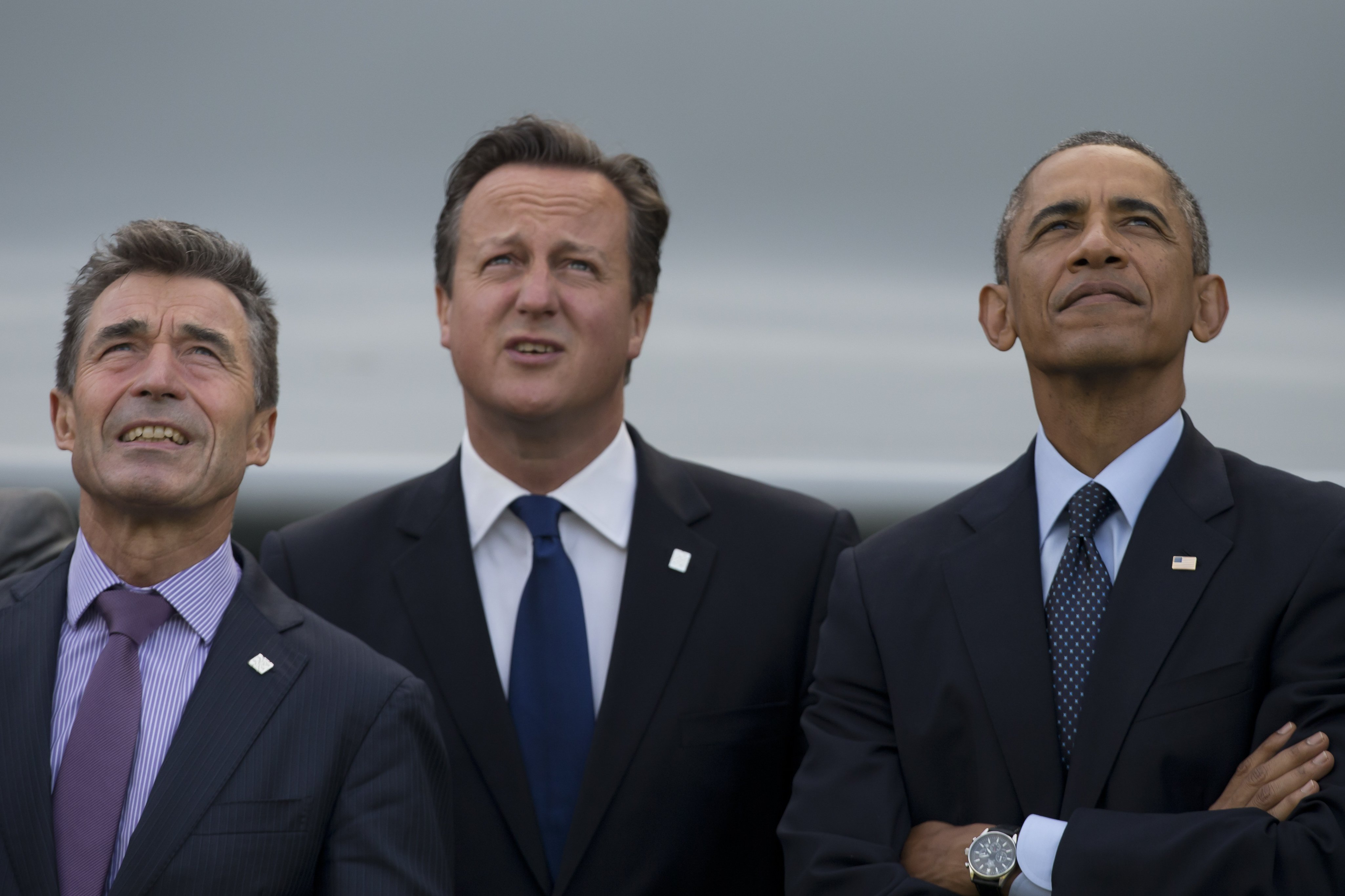 U.S. President Barack Obama, right, stands alongside British Prime Minister David Cameron, centre, and NATO Secretary General Anders Fogh Rasmussen during a flypast at the NATO summit at the Celtic Manor Resort in Newport, Wales on  Sept. 5, 2014.