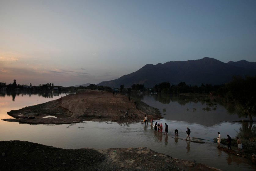 Kashmiri flood victims wade through receding flood waters as they walk back after collecting relief material in village Teing near Srinagar, India, Sept. 14, 2014.