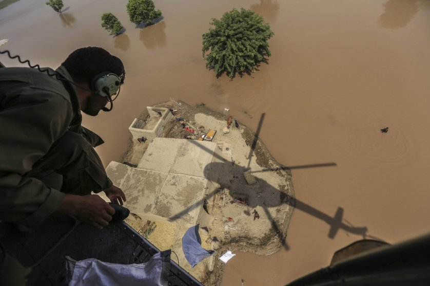 A Pakistani Army soldier distributes food bags in flooded areas in Shujabad, on the outskirts of Multan, Pakistan, Sept. 15, 2014.