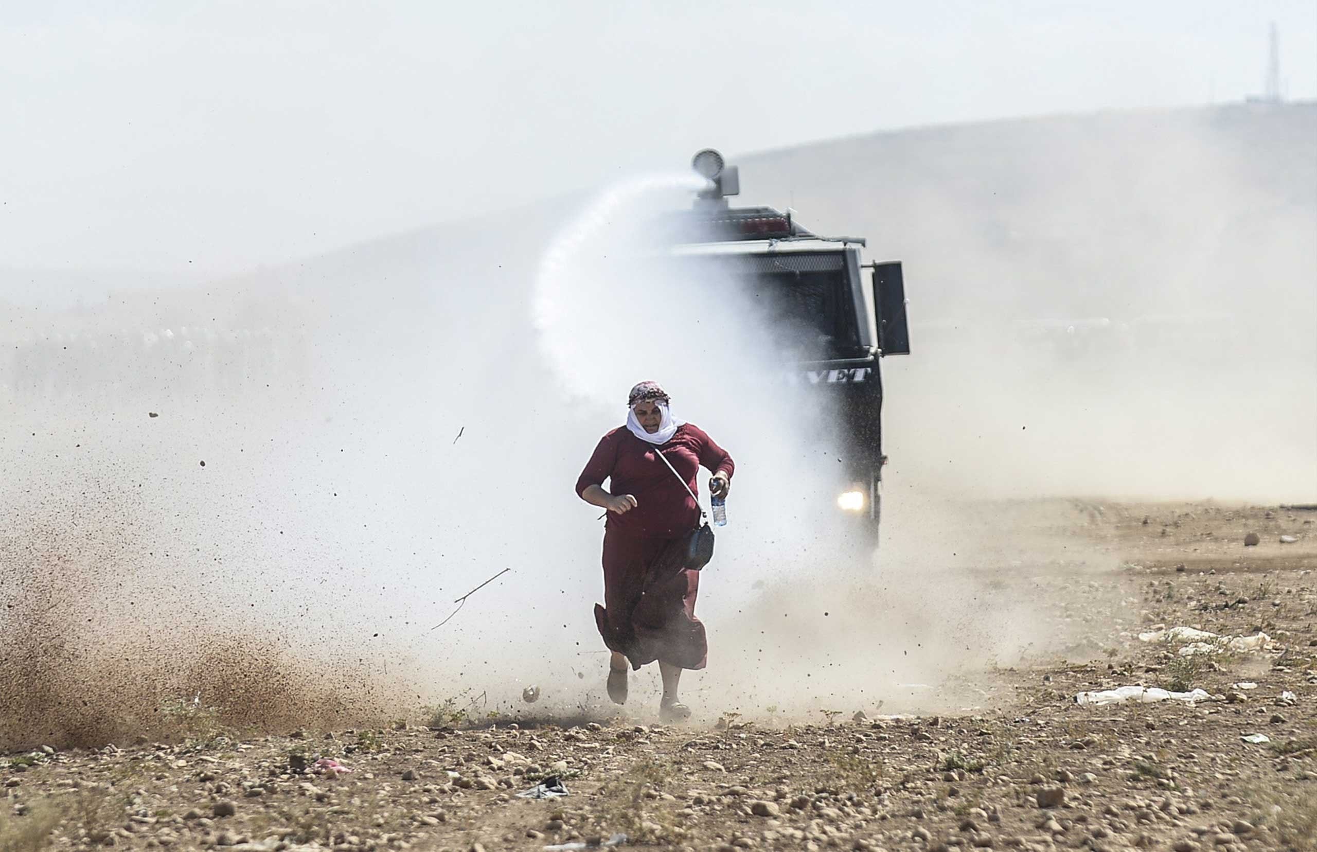 Sept. 22, 2014. A Kurdish woman runs away from a water cannon near the Syrian border after Turkish authorities temporarily closed the border at the southeastern town of Suruc in Sanliurfa province, Turkey.