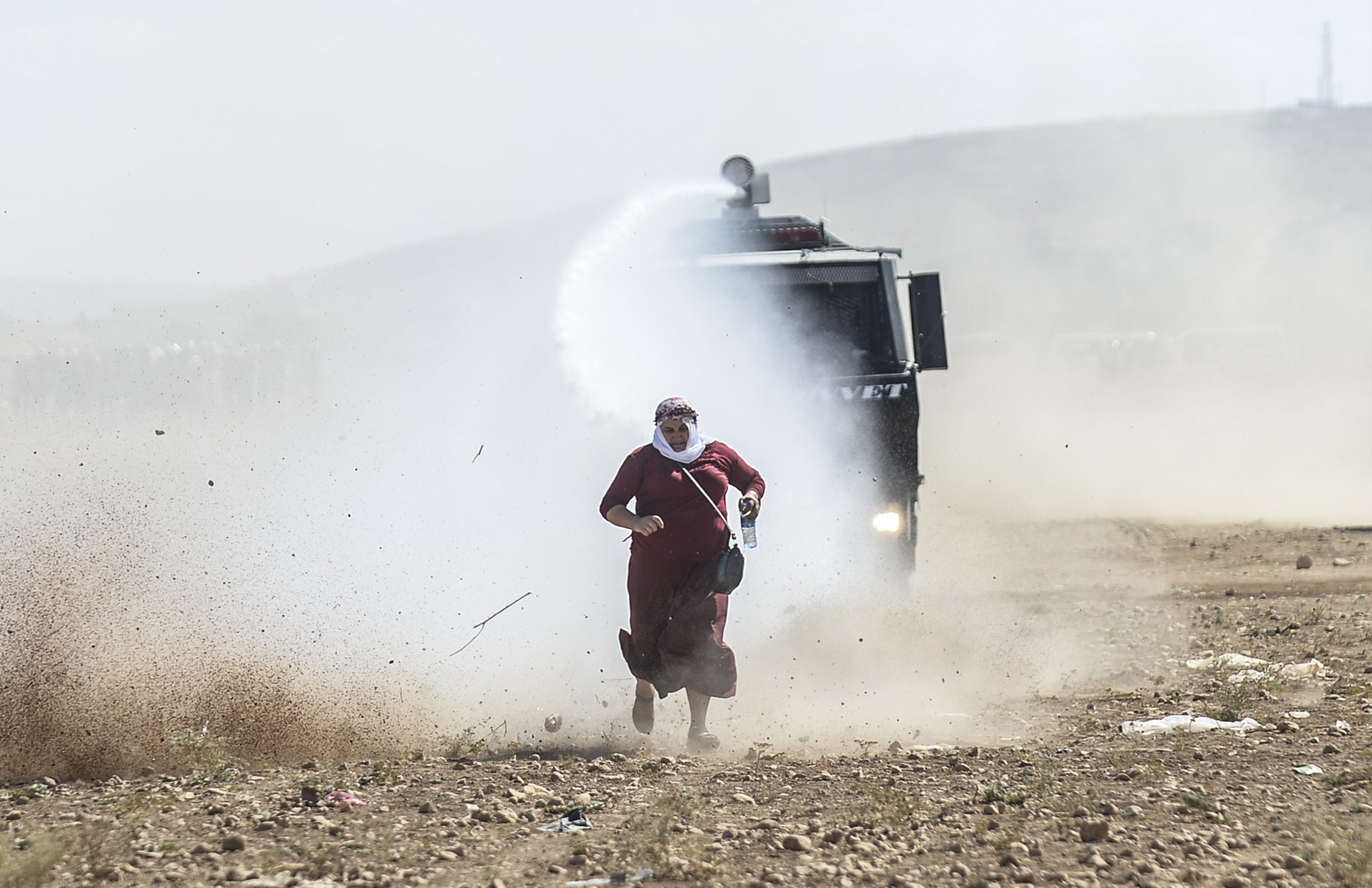 A Kurdish woman runs away from a water cannon near the Syrian border after Turkish authorities temporarily closed the border at the southeastern town of Suruc in Sanliurfa province, on Sept. 22, 2014.
