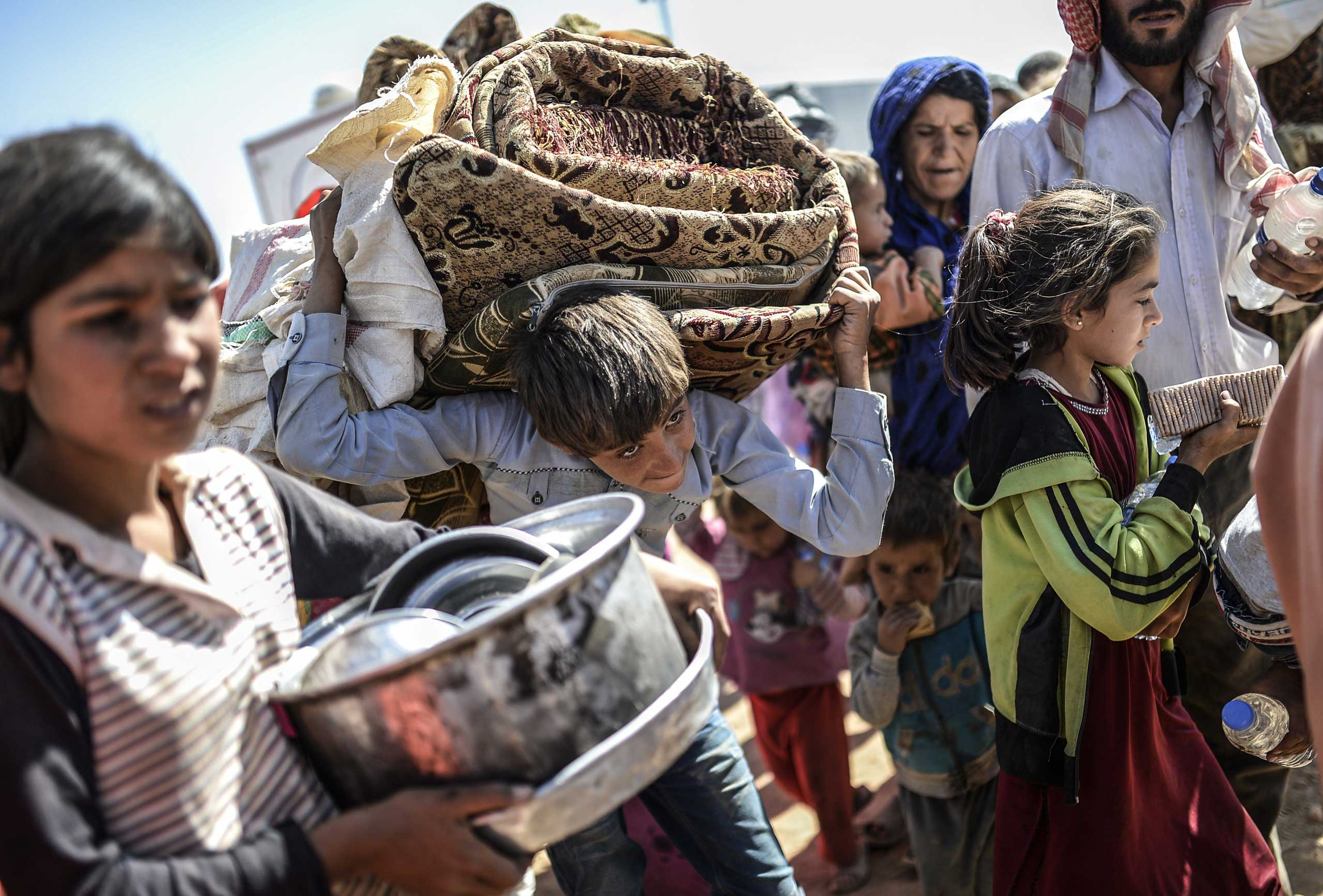 Sept. 23, 2014. Syrian Kurds carry their belongings as they cross the border between Syria and Turkey at the southeastern town of Suruc in Sanliurfa province.