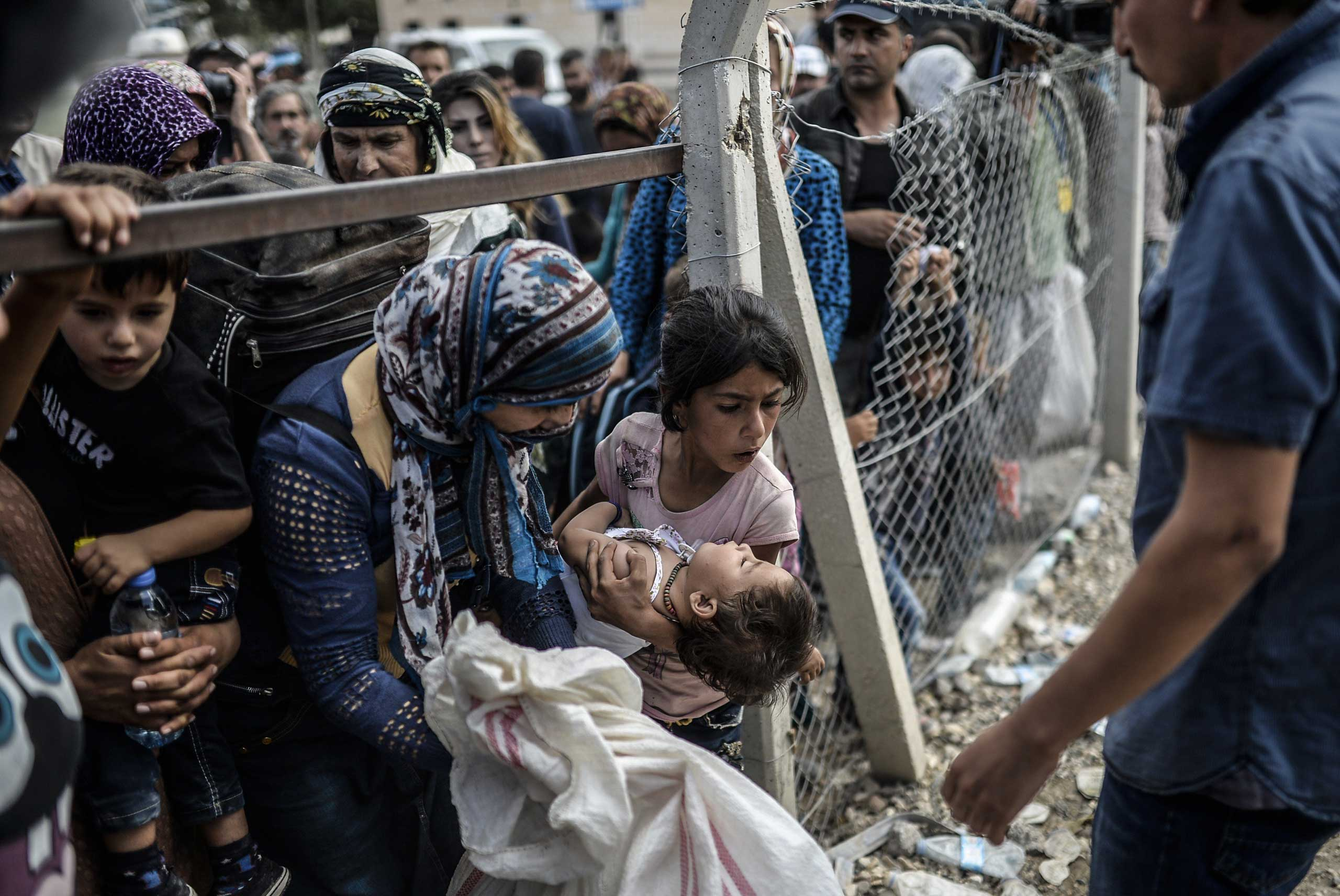 Sept. 24, 2014. Syrian Kurds go back to Syria at Mursitpinar crossing gate at the southeastern town of Suruc in Sanliurfa Province, Turkey.