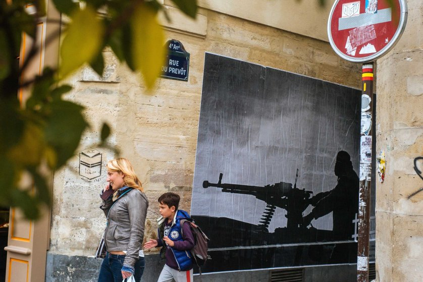 A woman and a child walk in front of one of Thibaut Camus' photographs on Rue du Prevot, Paris.