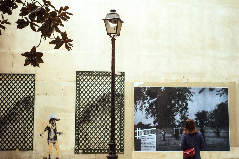 A woman stands in front of one of Pierre Terdjman's photographs in Paris.