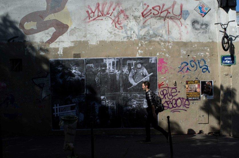 A man walks in front of Benjamin Girette's portraits shot in Ukraine in Feb. 2014