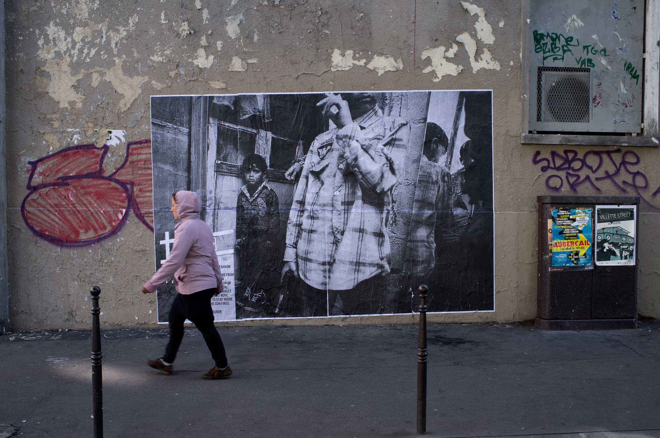 A woman walks in front of one of Zacharie Scheurer's photographs shot in Lebanon.