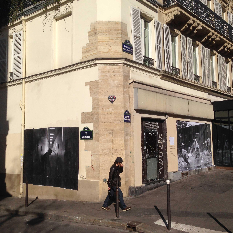 A man walks between two of Pierre Terdjman's photographs in Paris.