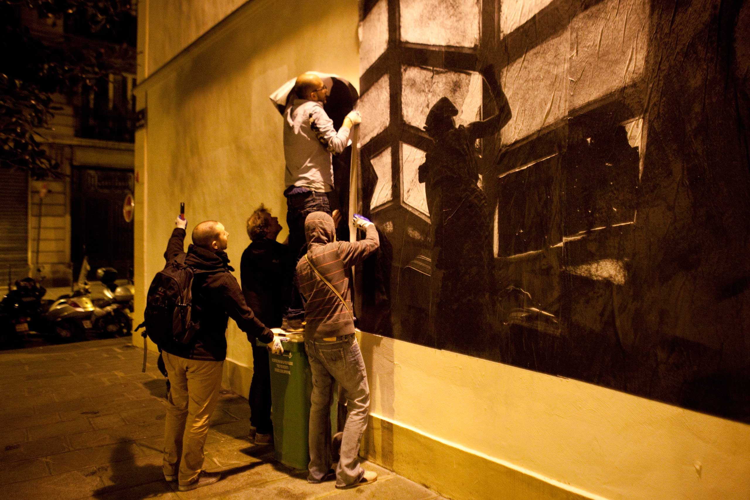 French photographer Pierre Terdjman, helped by friends and colleagues, puts up one of his images on a Parisian wall in France