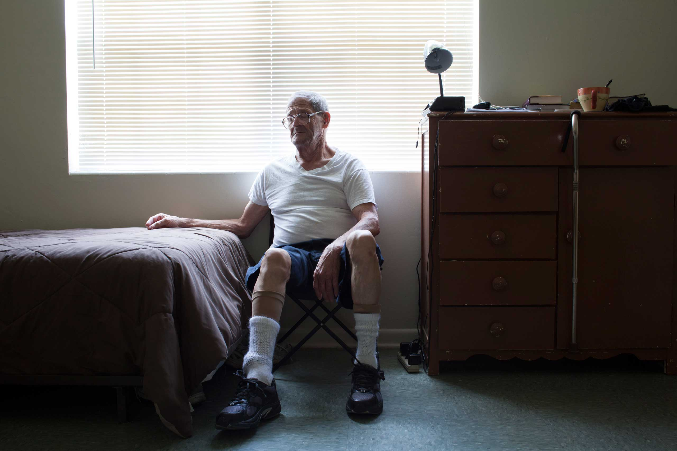 """Paul sitting beside his bed in his new home right after being released from prison. He has been a resident of Miracle Village for over a year """"There is no judging, for those who are here have the same name."""