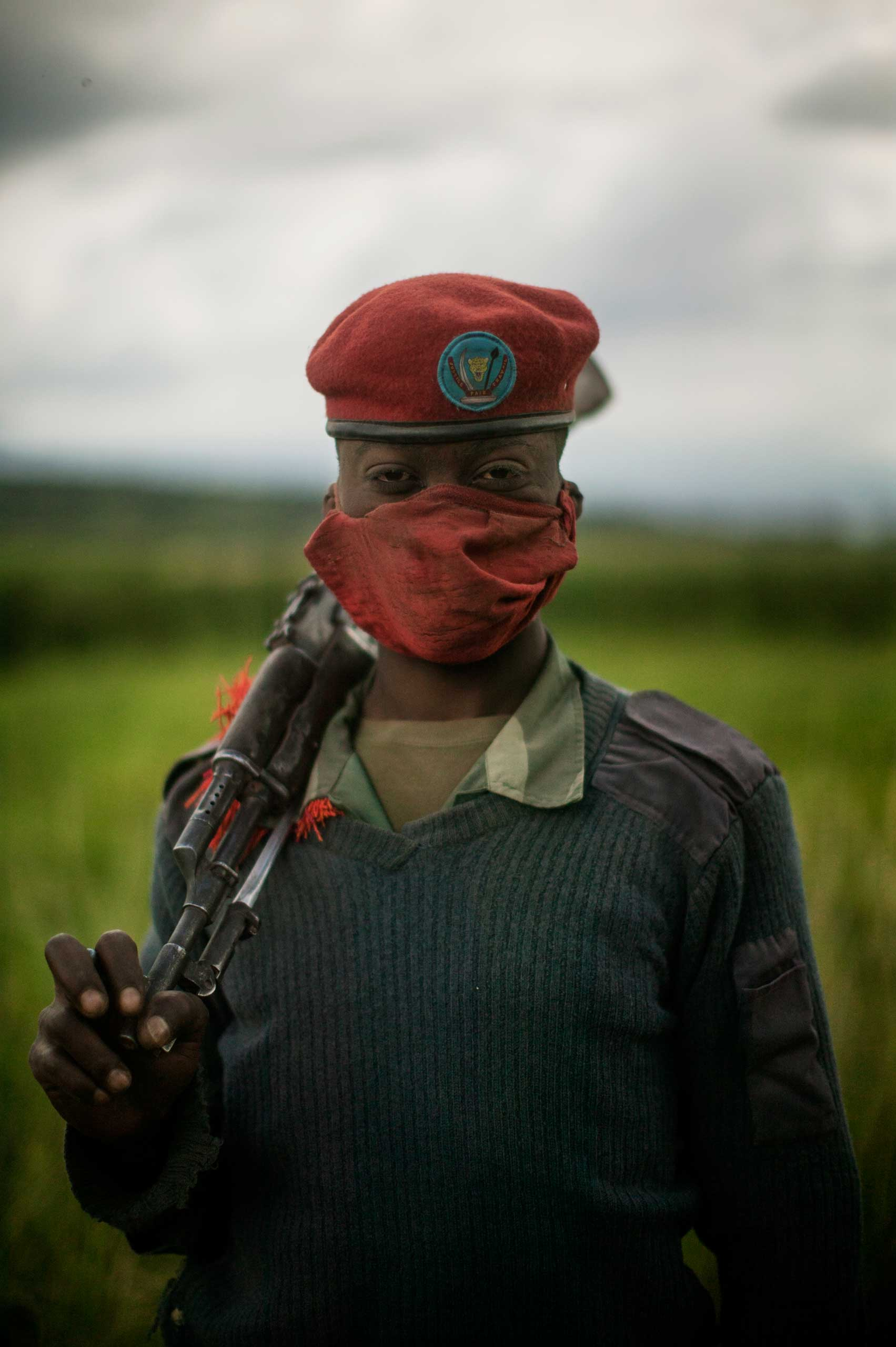 An unnamed Congolese soldier stands for a portrait in a village in North Kivu province.
