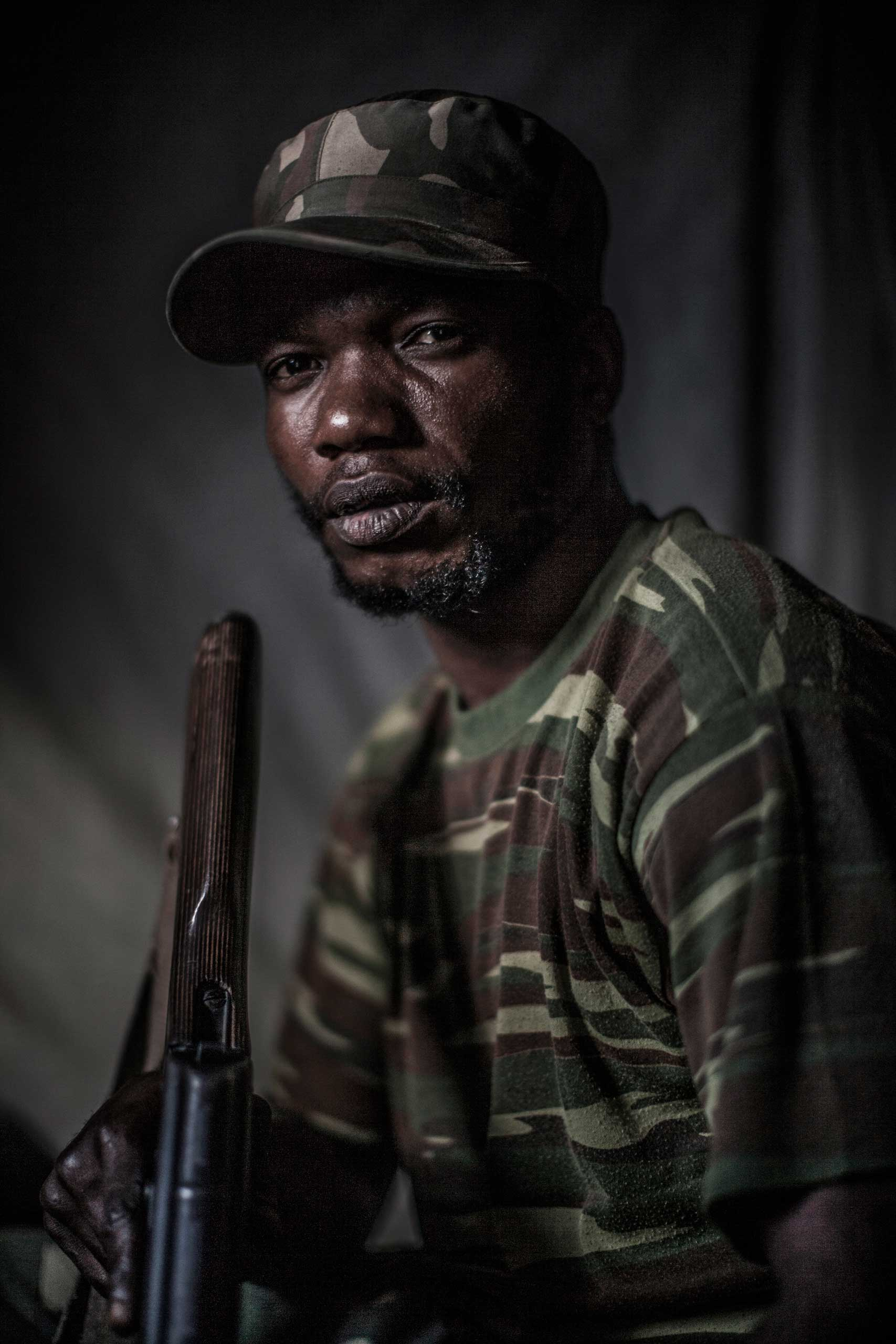 An unnamed Congolese soldier sits for a portrait in a village in North Kivu province.