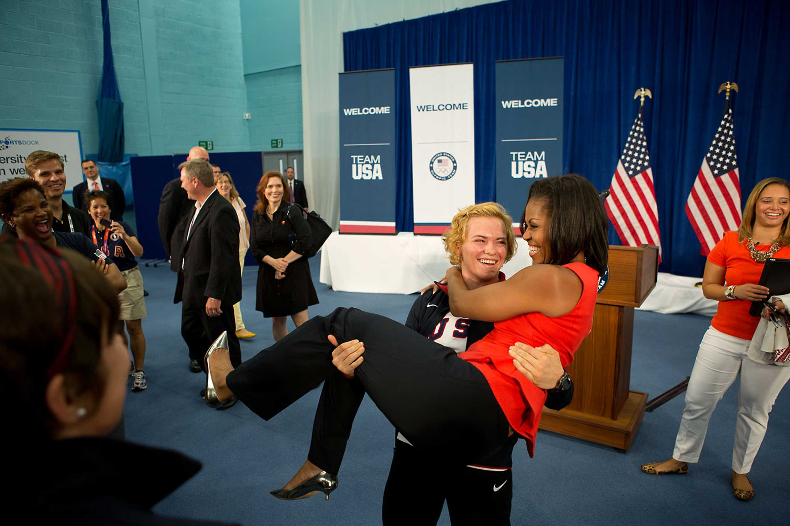 U.S. Olympic wrestler Elena Pirozhkova picks up the First Lady during a greet with Team USA Olympic athletes competing in the 2012 Summer Olympic Games, at the U.S. Olympic Training Facility at the University of East London in London, England, July 27, 2012.
