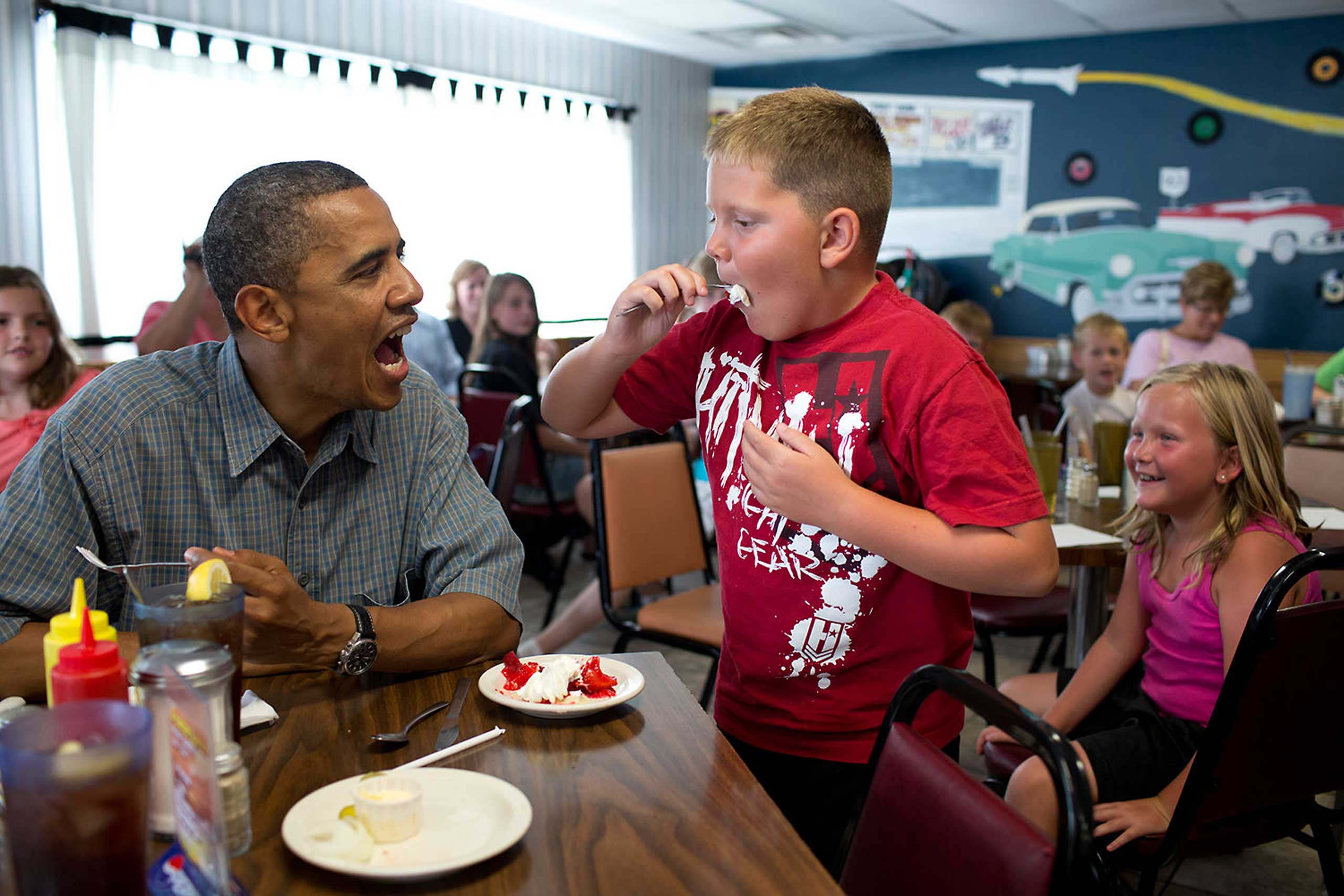 President Obama shares a piece of strawberry pie with a young patron at Kozy Corners, a local diner in Oak Harbor, Ohio, July 5, 2012.