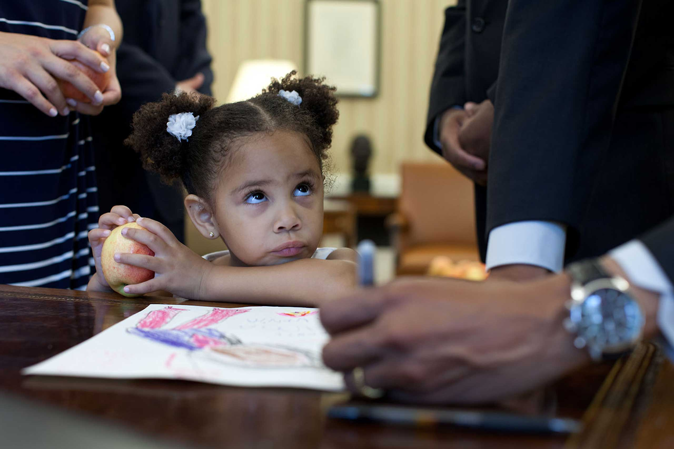 Luz Graham-Urquilla, 4, watches President Obama as he signs her drawing at the Resolute Desk in the Oval Office, May 25, 2012.