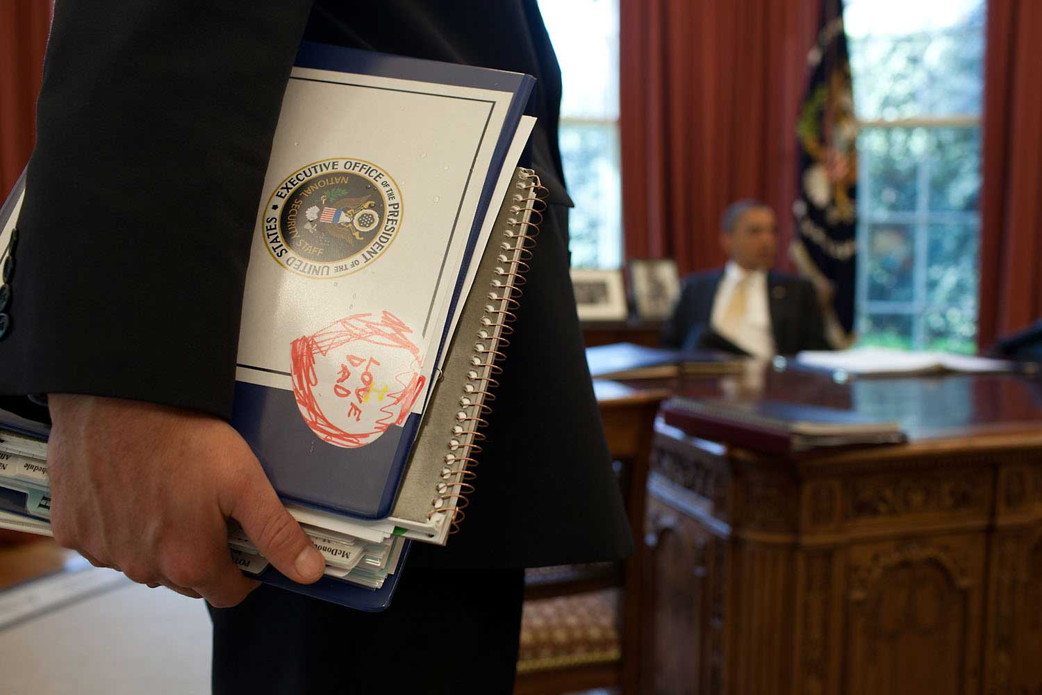 Denis McDonough, Deputy National Security Advisor, holds a binder with a note from his son as he and others brief President Obama in the Oval Office, March 29, 2012.