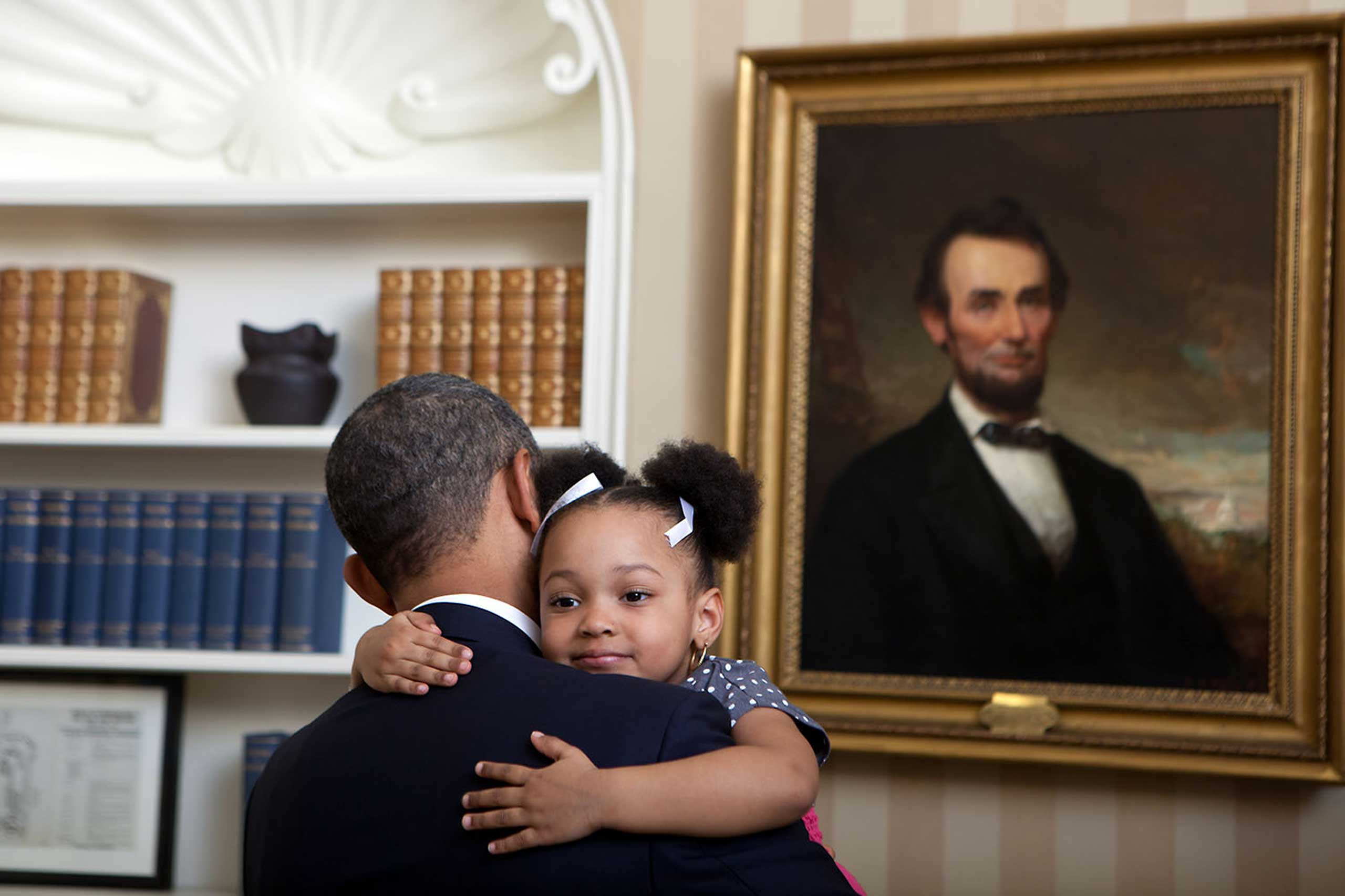 President Obama greets the daughter of national security staffer during a departure photo in the Oval Office, Feb. 1, 2012.