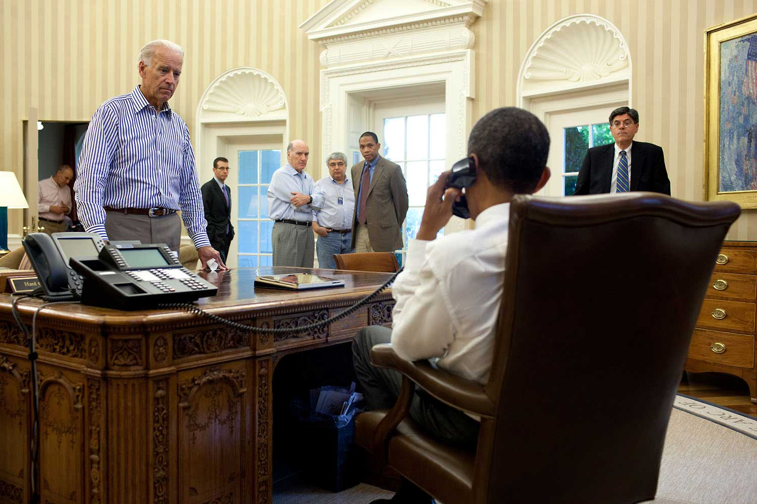 The Vice President and other staff watch and listen as the President talks on the phone in the Oval Office with Senate Majority Leader Harry Reid during the debt limit and deficit discussions, July 31, 2011.